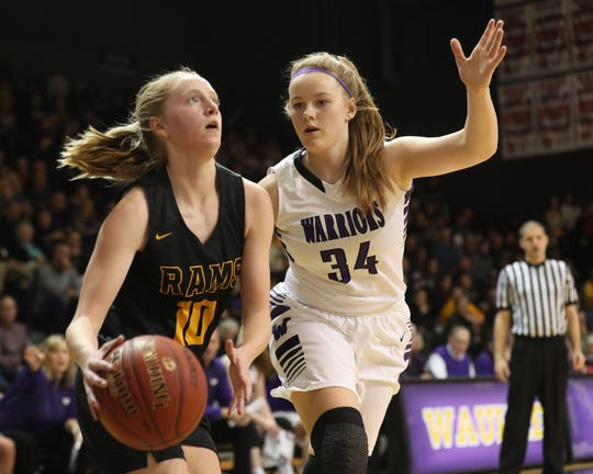 Southeast Polk's Grace Larkins (10) drives baseline against Waukee's Megan Earney (34) on Friday, Dec. 21, at Waukee High School. Southeast Polk won the game 74-41.