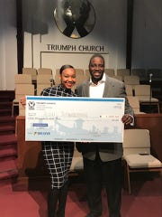 "Aini Robertson, the 2017 valedictorian of Cass Technical High School and current University of Michigan college student receives a $1,000 scholarship from Triumph Church as part of the 2018 ""BIG GIVE Weekend"" in the days leading up to Christmas. She stands with Rev. Solomon Kinloch, Jr. the senior pastor at Triumph Church."