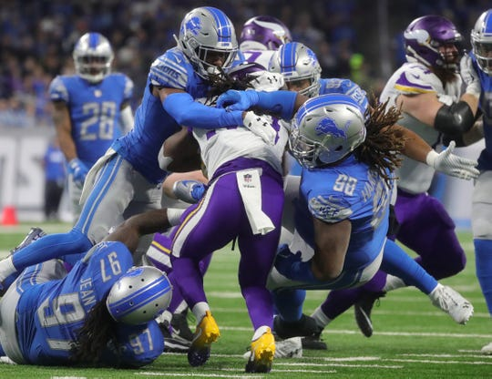 Detroit Lions defenders tackle Minnesota Vikings running back Latavius Murray during the second half at Ford Field in Detroit on Sunday, December 23, 2018.