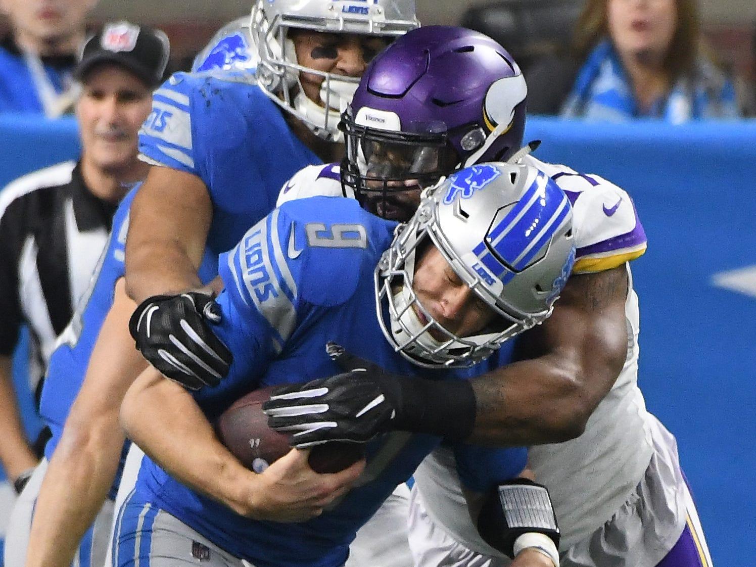 Lions quarterback Matt Stafford is sacked by Vikings' Jaleel Johnson in the third quarter.