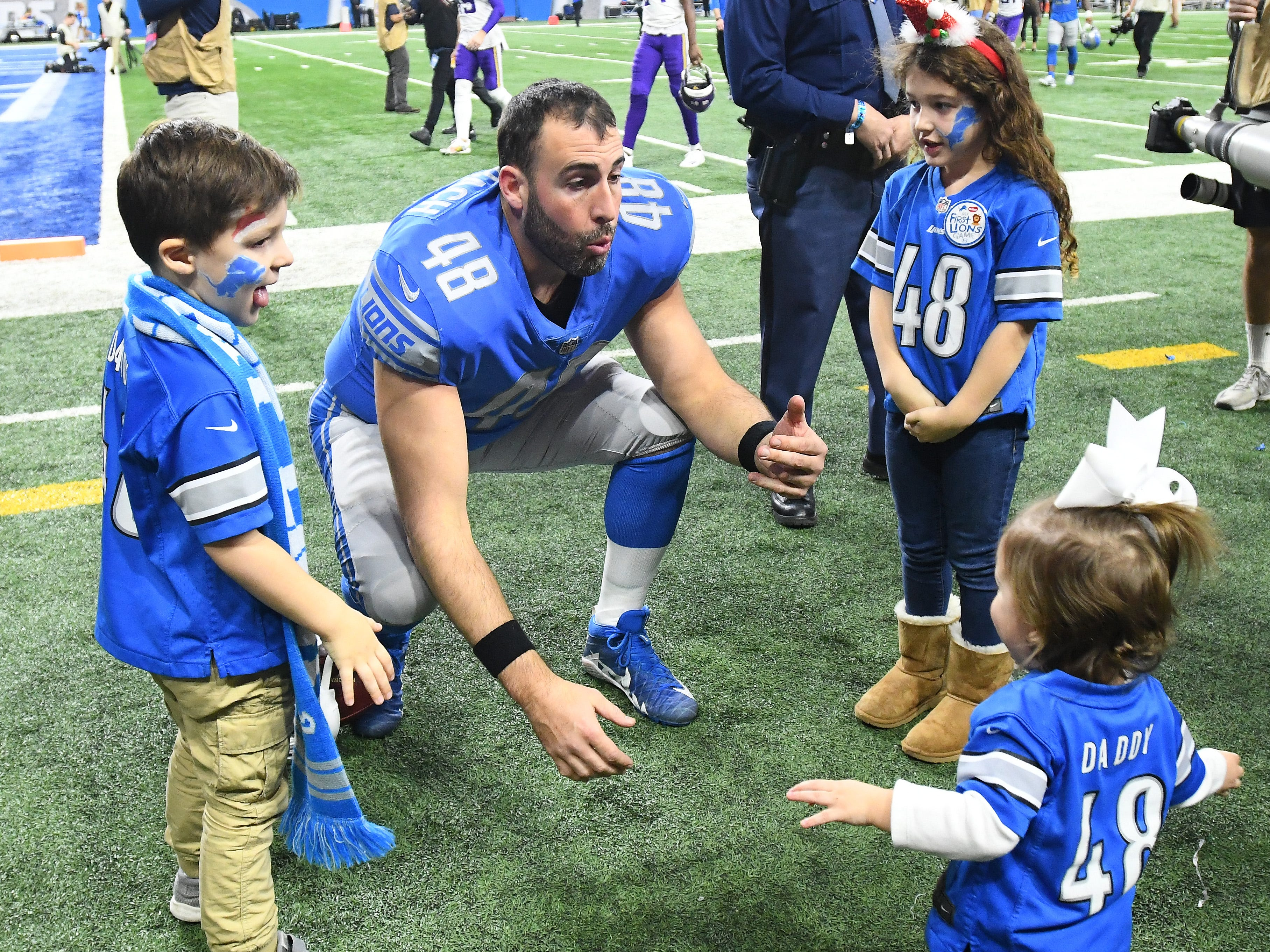 Lions 15 year veteran long snapper Don Muhlbach plays with his kids on the field after Detroit lost their last home game to the Vikings.