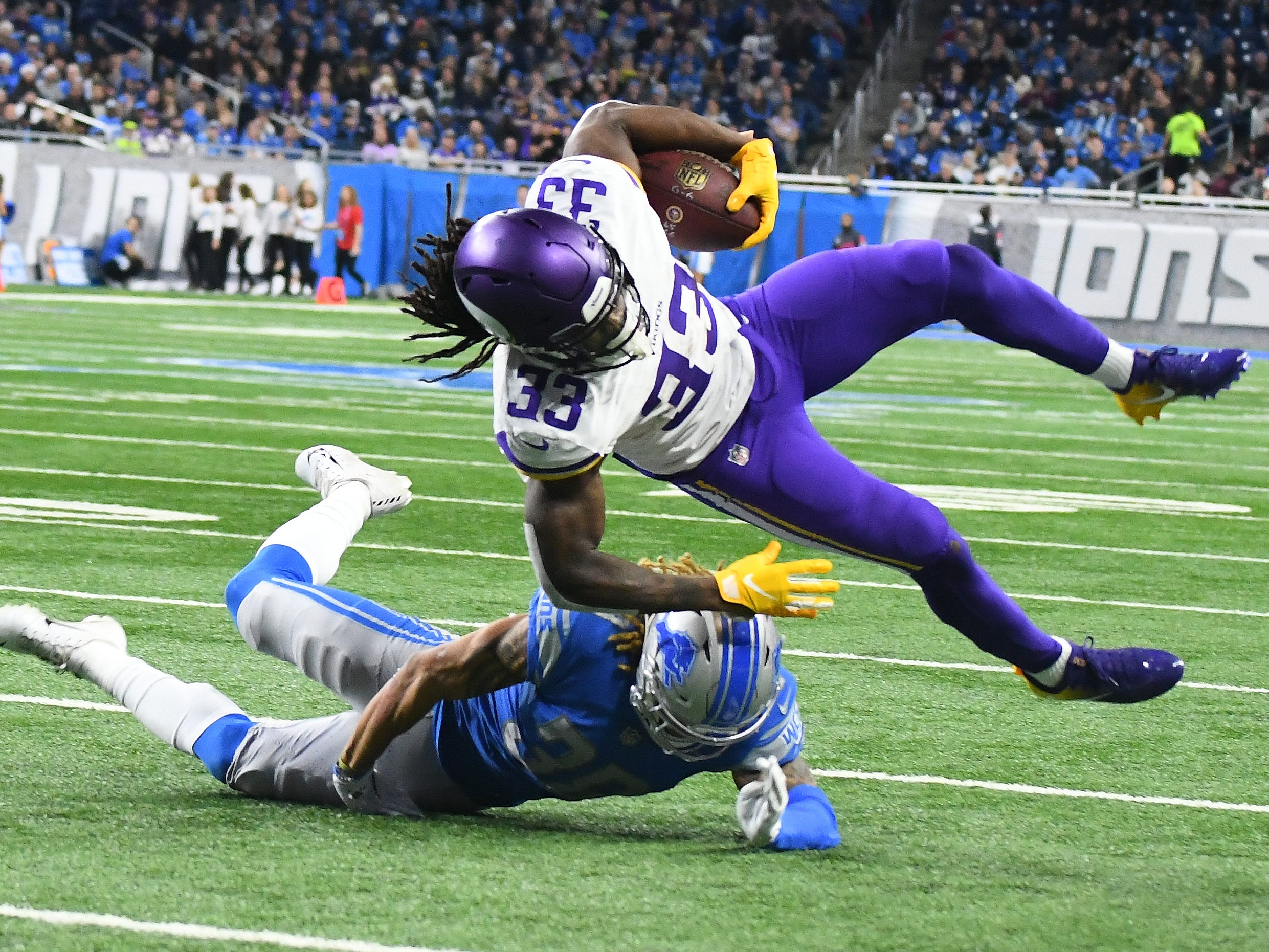 Vikings' Dalvin Cook is upended by Lions' Mike Ford in the second quarter.