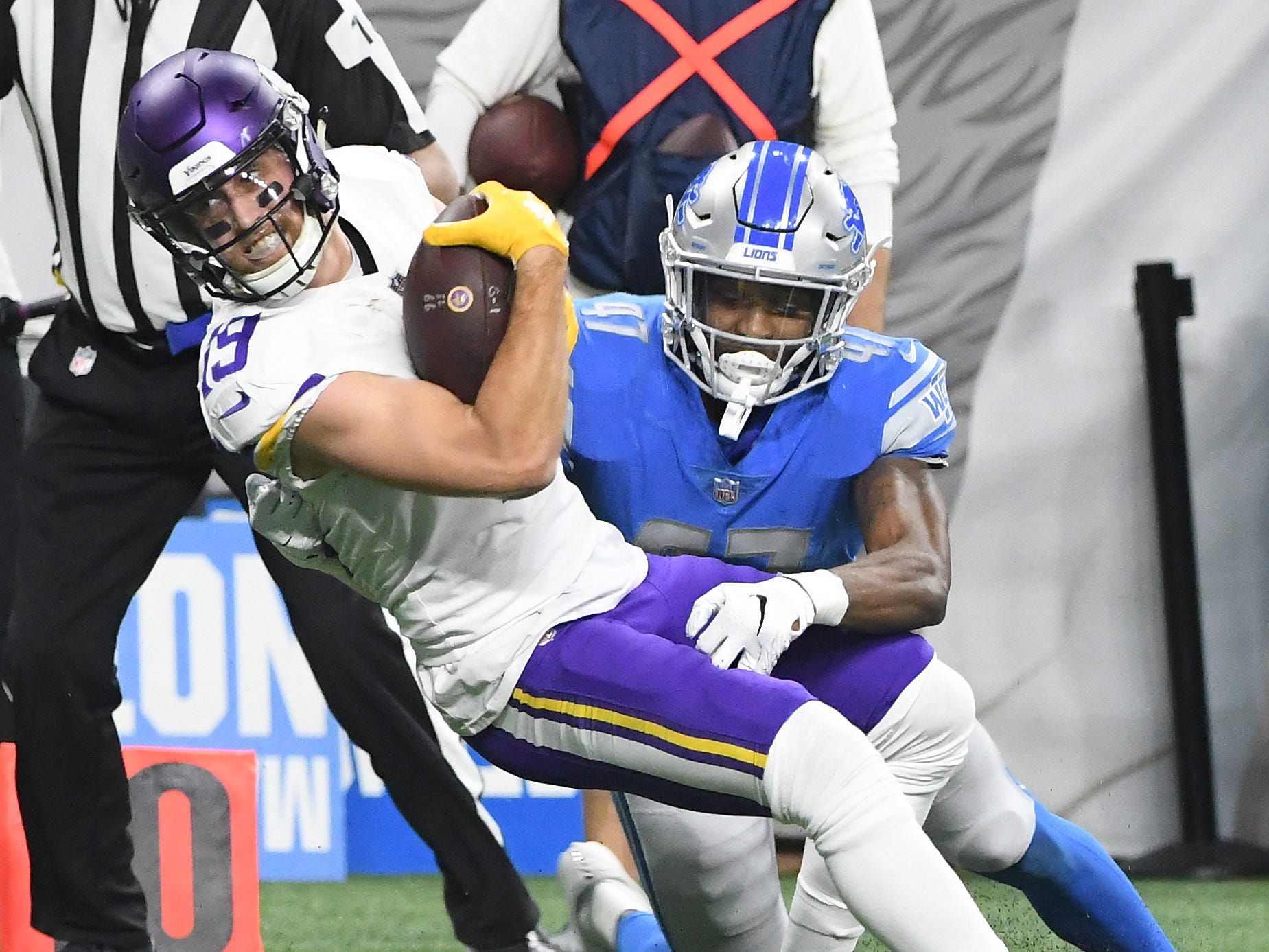 Vikings' Adam Thielen is brought down by Lions' Tracy Walker in the third quarter.