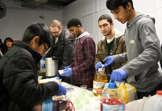 From left, Aadam Ahmed, 12, Matt Bailey, Issa Saadiq (cq), 13, Bilal Kawsara, 21, and Safwan Ahmed, 16, all of Detroit, serve juices and coffee. Muslim volunteers organized by the Michigan Muslim Community Council serve food and drink at the NSO Tumaini Center in Detroit on Dec. 23, 2018.   (Robin Buckson / The Detroit News)