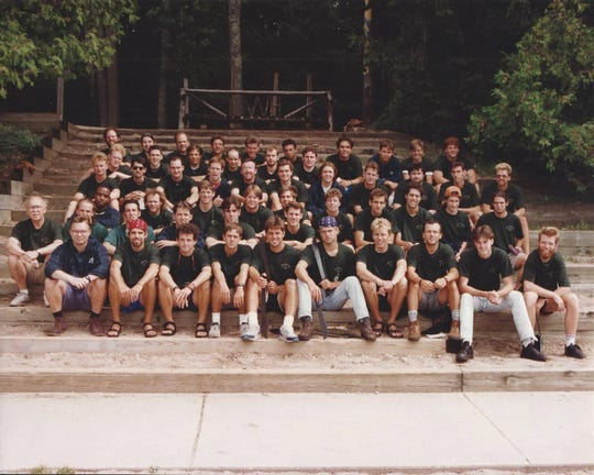 Pat Rode, seated second row, far left, with his 1993 staffers, on the steps of the Torch Lake waterfront. Here, Rode liked to open his mail after lunch while talking with any campers who came up to chat with him.