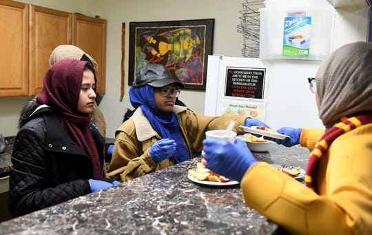 From left, Mahjaein Manik, 17, and Malaikan Saadiq, 16, both of Detroit, give food to fellow volunteer Siham Azom, 15, to serve at the NSO Tumaini Center. Muslim volunteers organized by the Michigan Muslim Community Council serve food and drink at the NSO Tumaini Center in Detroit on Sunday.