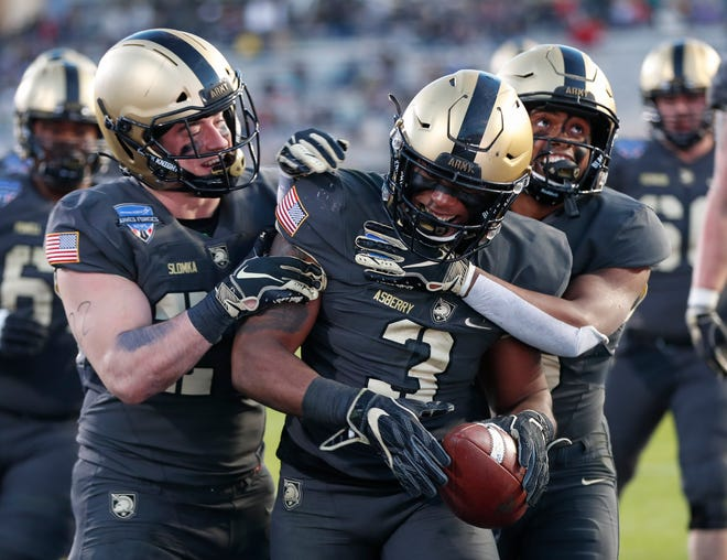 Army running back Jordan Asberry (3) celebrates his touchdown with wide receiver Glen Coates, right, and running back Connor Slomka, left, during the second half Saturday of the Armed Forces Bowl in Fort Worth, Texas. Army won 70-14.