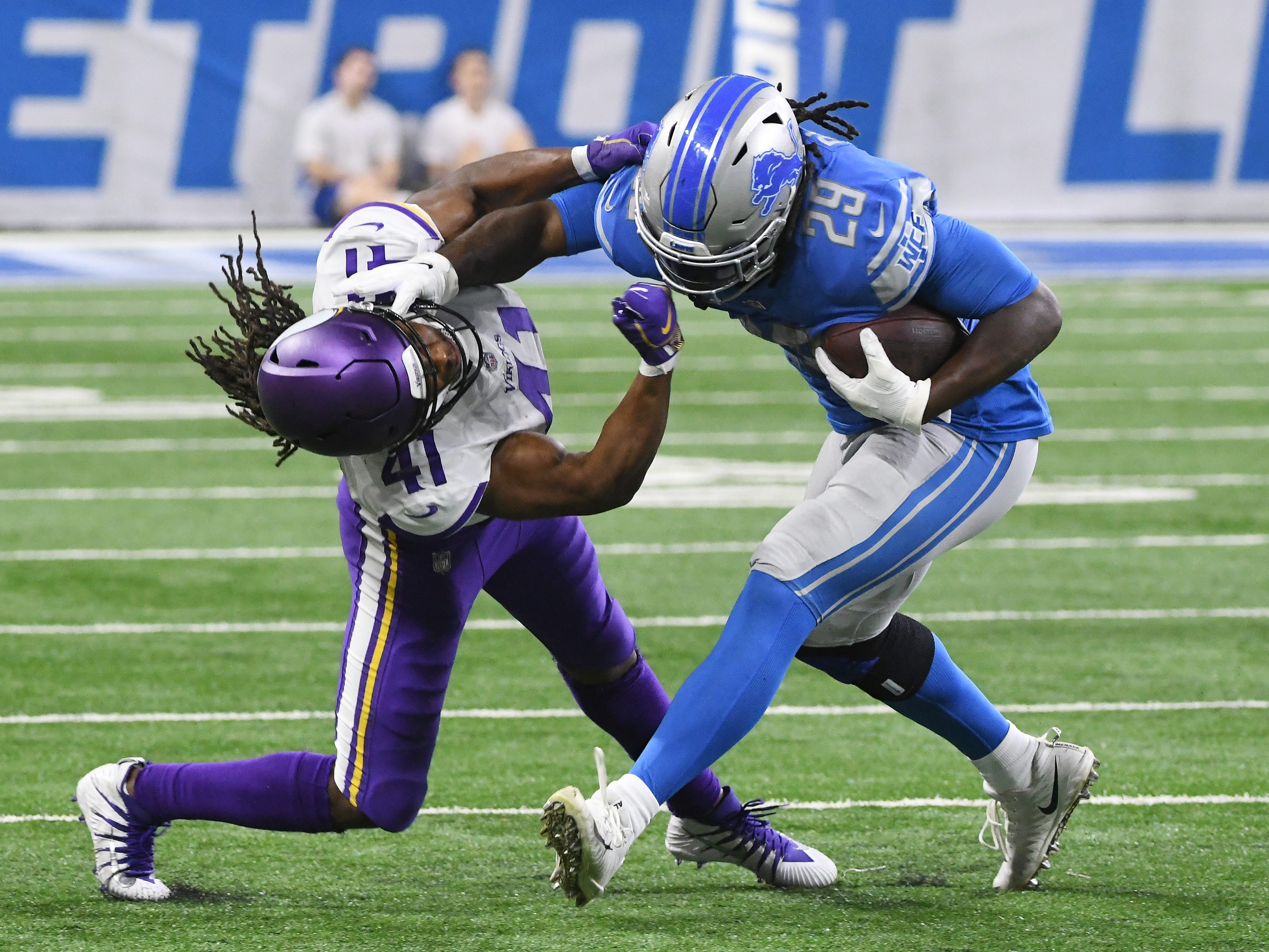 Vikings' Anthony Harris is thrown to the ground by Lions' LeGarrette Blount but still is able to drag him down by his legs in the fourth quarter.