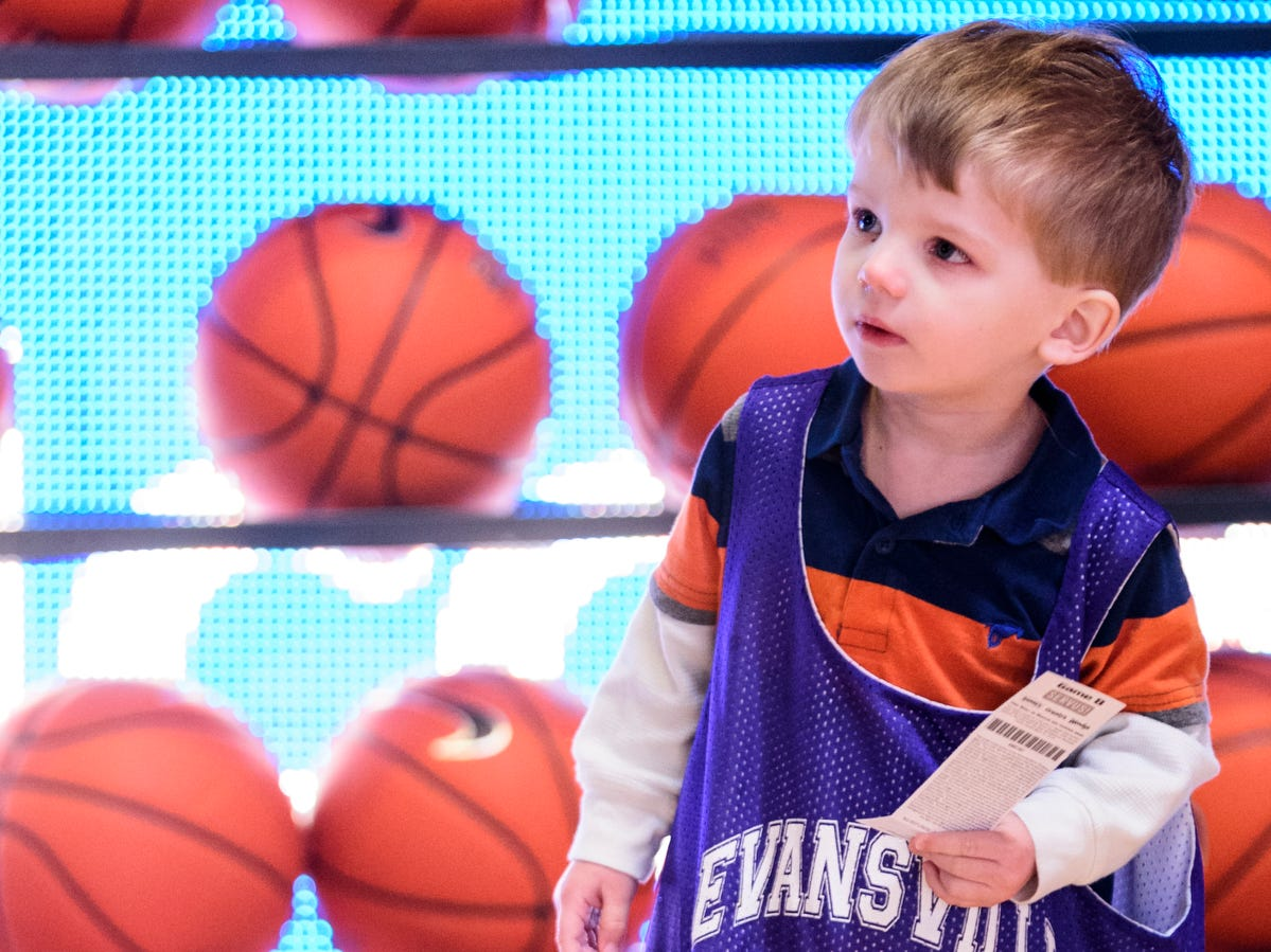 Two-year-old Leo Schmitt stands in line with other kids as they prepare to high-five all of players on the University of Evansville Purple Aces basketball team at Ford Center in Evansville, Ind., Saturday, Dec. 22, 2018. The Purple Aces defeated the University of Wisconsin-Green Bay Phoenix 80-75 in their last non-conference game of the season.