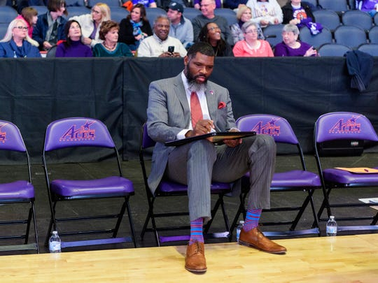 University of Evansville Head Coach Walter McCarty makes notes before his team takes on the University of Wisconsin-Green Bay Phoenix at Ford Center in Evansville, Ind., Saturday, Dec. 22, 2018. The Purple Aces defeated the Phoenix 80-75 in their last non-conference game of the season.