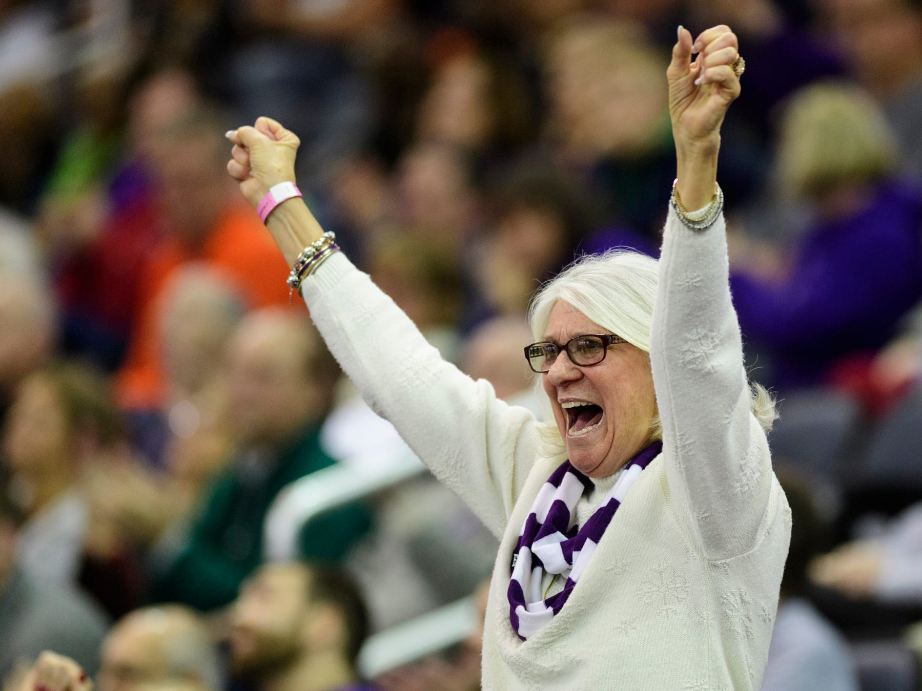 Phyllis Steber cheers for the University of Evansville Purple Aces as they secure their lead over the University of Wisconsin-Green Bay Phoenix with less than a minute left in the game at Ford Center in Evansville, Ind., Saturday, Dec. 22, 2018. The Purple Aces defeated the Phoenix 80-75 in their last non-conference game of the season.