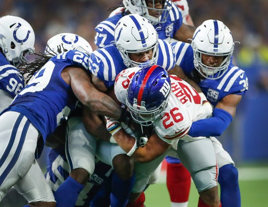 New York Giants running back Saquon Barkley (26) is stopped by Indianapolis Colts outside linebacker Darius Leonard (53), George Odum (30) and Malik Hooker (29) in the second half of their game at Lucas Oil Stadium on Sunday, Dec. 23, 2018. The Colts defeated the Giants 28-27.