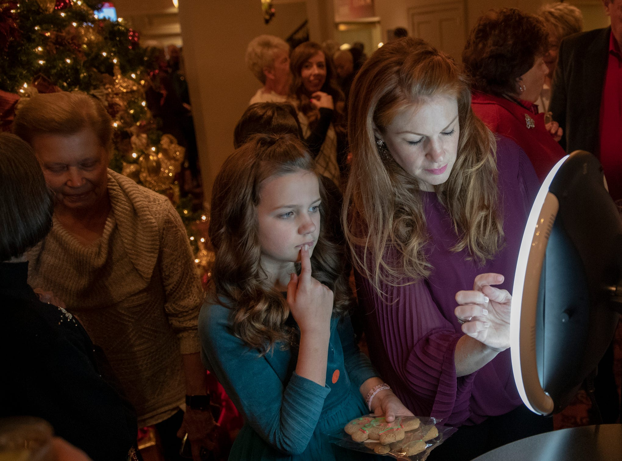 Maren Smith, 9, and her mother Melissa Smith, Carmel, work with a selfie station that's in the lobby at Yuletide Celebration, showcasing the Indianapolis Symphony Orchestra, at Hilbert Circle Theater, Indianapolis, Sunday. Dec. 23, 2018. The extravaganza features dancing, holiday songs, and skits.