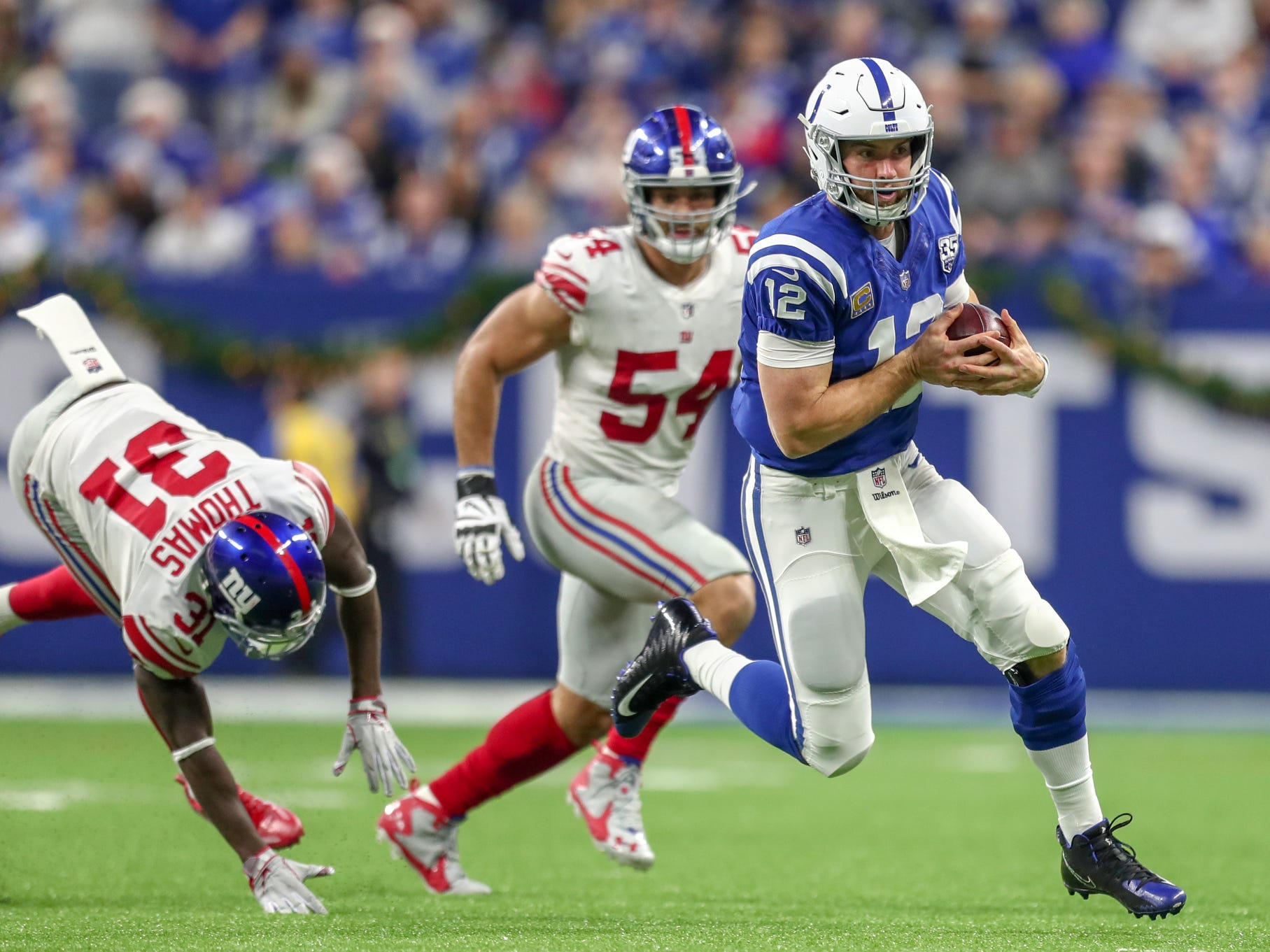 Indianapolis Colts quarterback Andrew Luck (12) takes off on a run for the first down against the New York Giants at Lucas Oil Stadium in Indianapolis on Sunday, Dec. 23, 2018.