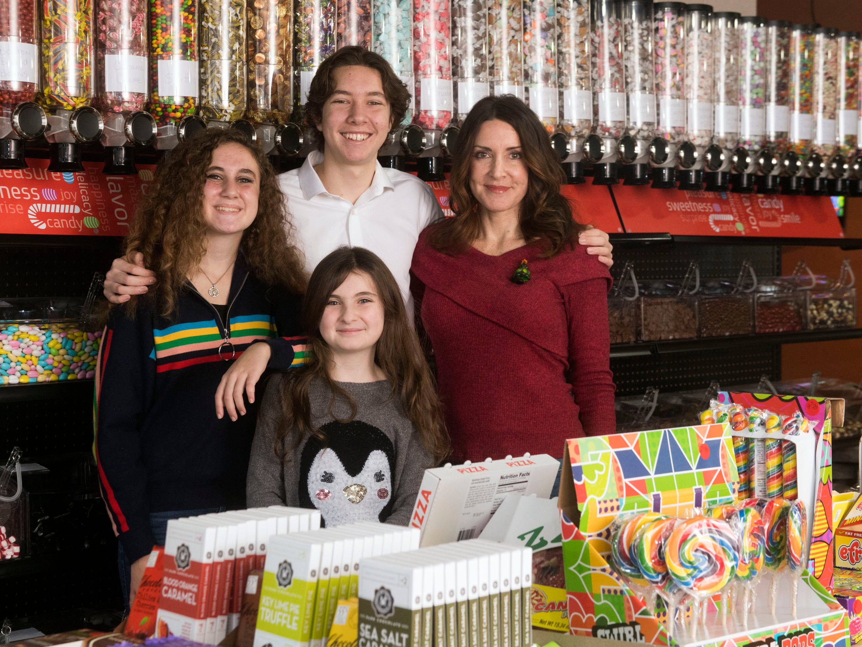 Lisa Henderson, right, and her children, Dov, 17, Ela, 14, and Abby, 9, spend time at their new candy shop, Gimme Sugar, at Homberg Place on Friday, Dec. 21, 2018.