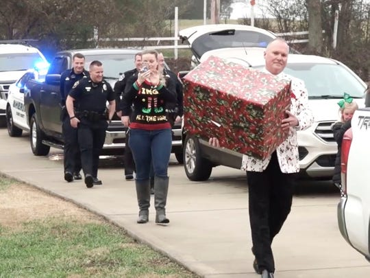 The Blount County Sheriff's deputies  Maryville resident Kyle Kostowicz with Christmas gifts during a visit to his home on Sunday. December 23, 2018. Kyle helped save his mother, Bethany Kostowicz's, on left, life by calling 911 when he found her unresponsive.