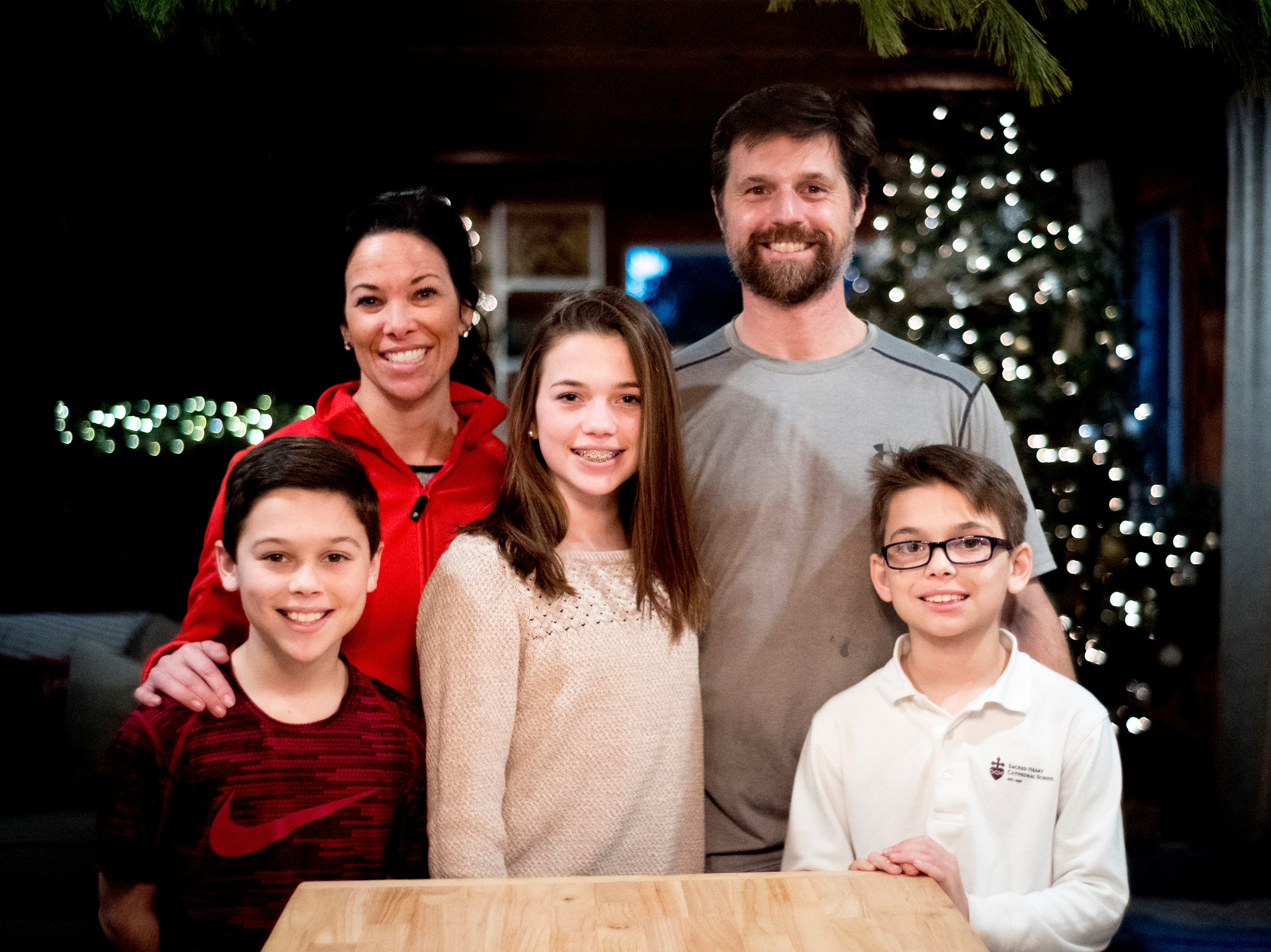 From left, 11-year-old Baylor, mom Lydia, 13-year-old Olivia, dad Matt, and 9-year-old Waylon Greiner pose for a family photo inside their home on Breezy Ridge Trail in West Knoxville, Tennessee on Thursday, December 20, 2018.