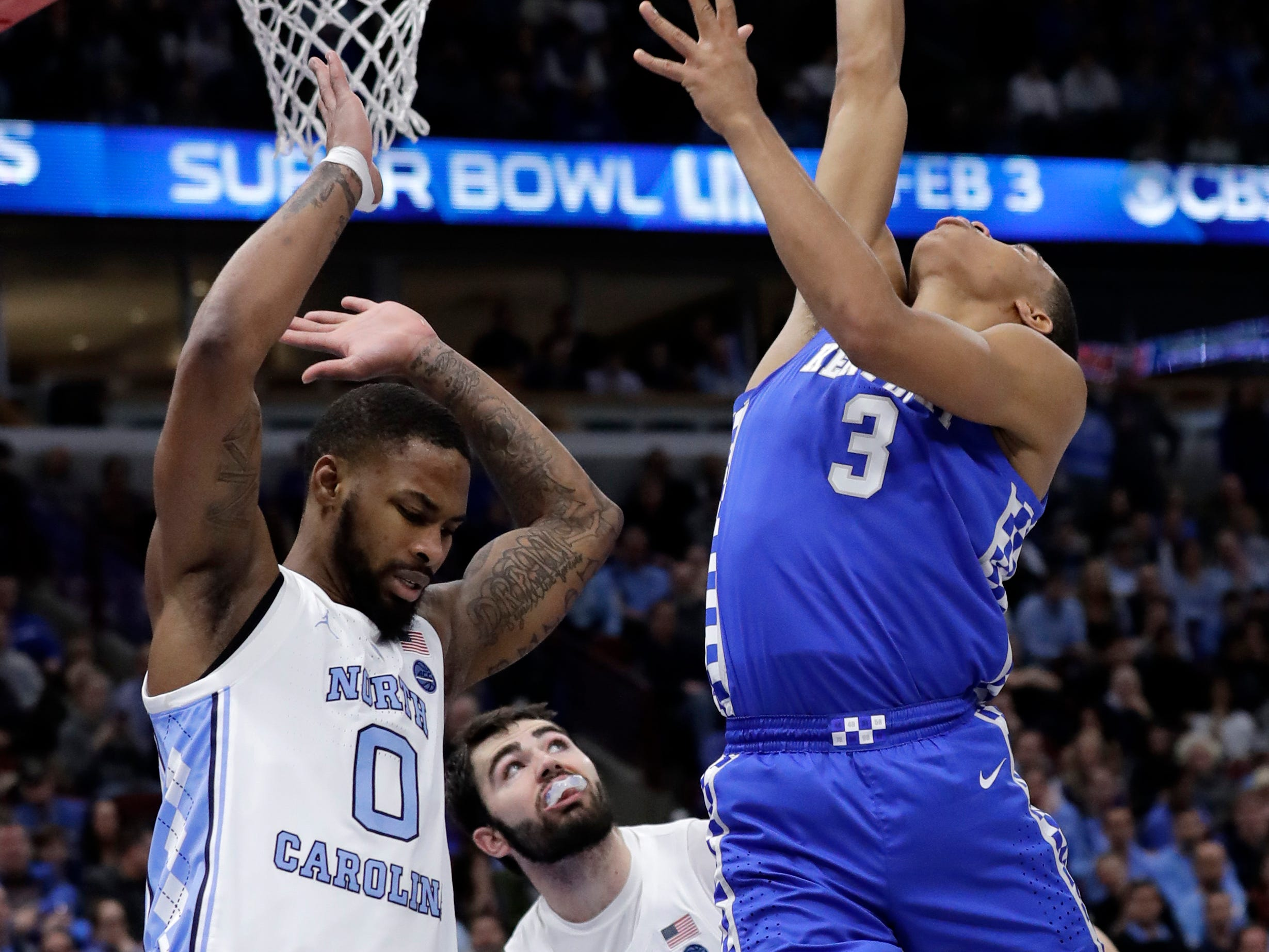 Kentucky guard Keldon Johnson, right, shoots over North Carolina guard Seventh Woods, left, during the second half of an NCAA college basketball game Saturday, Dec. 22, 2018, in Chicago. Kentucky won 80-72.