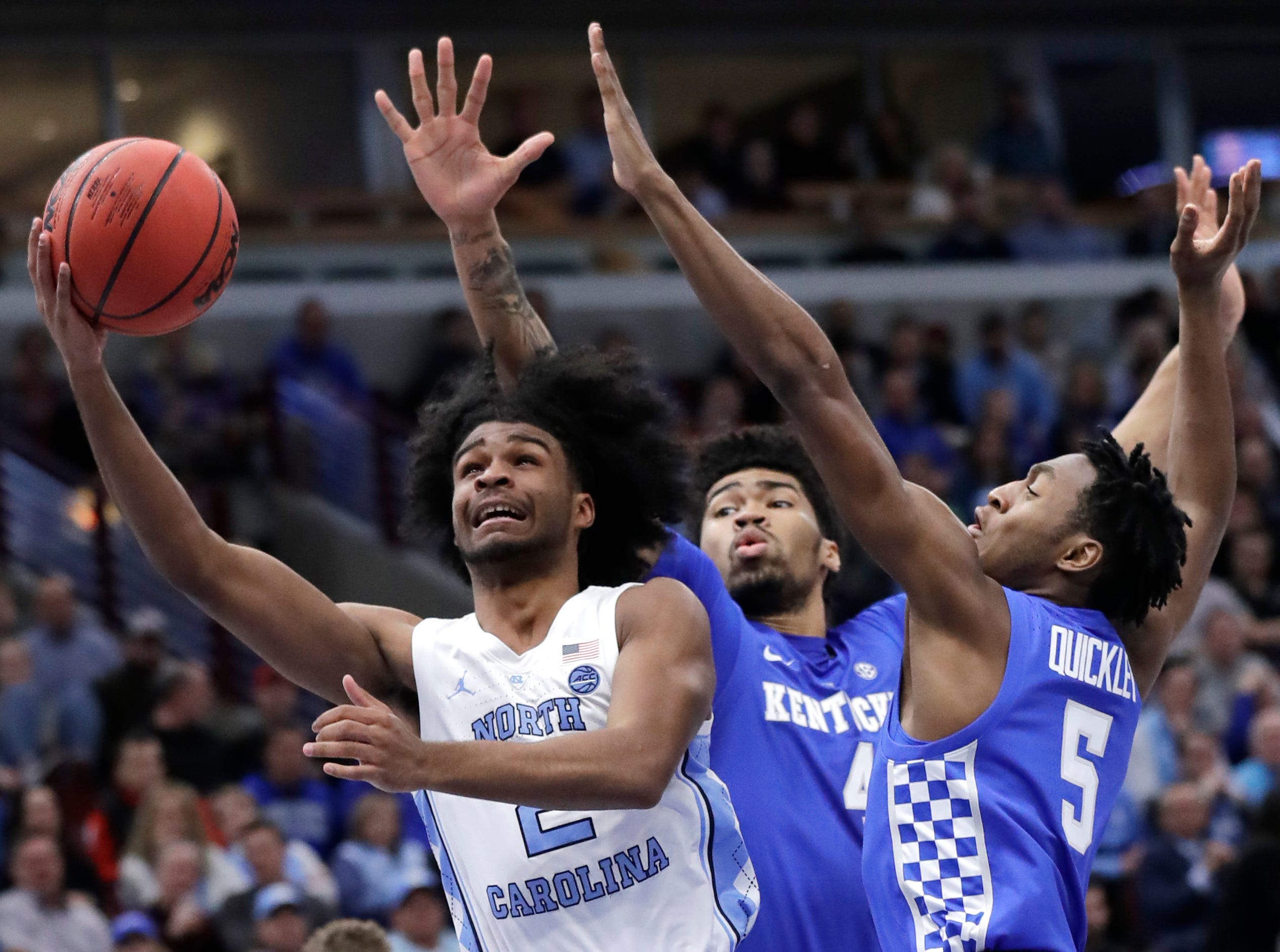 North Carolina guard Coby White, left, drives to the basket against Kentucky forward Nick Richards, center, and guard Immanuel Quickley during the first half of an NCAA college basketball game in the fifth annual CBS Sports Classic, Saturday, Dec. 22, 2018, in Chicago.