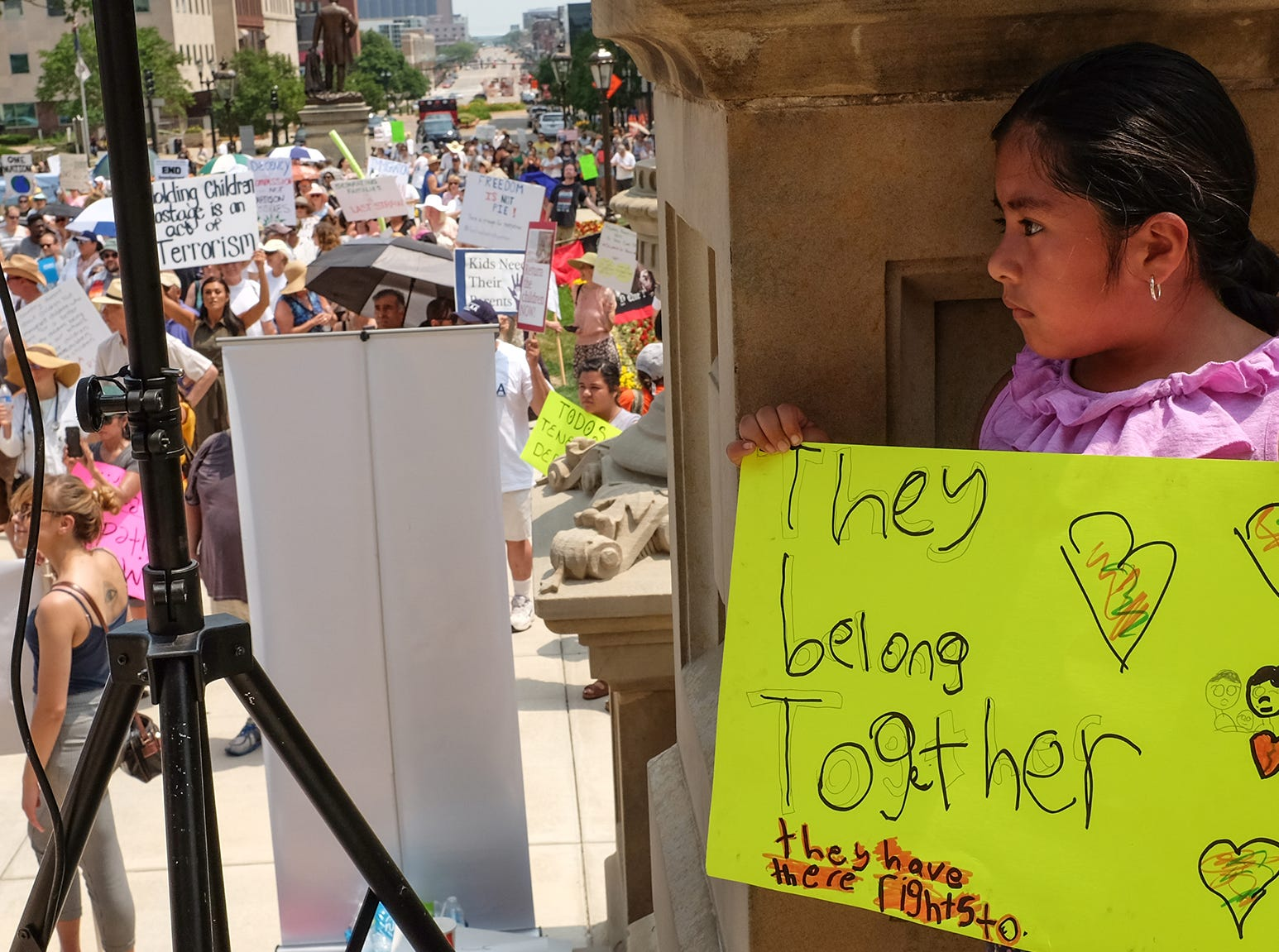 Camila Garcia, 7, from Lansing, peeks out at the crowd of over a thousand people at a Families Belong Together rally at the state Capitol in Lansing, Michigan on Saturday, June 30, 2018.