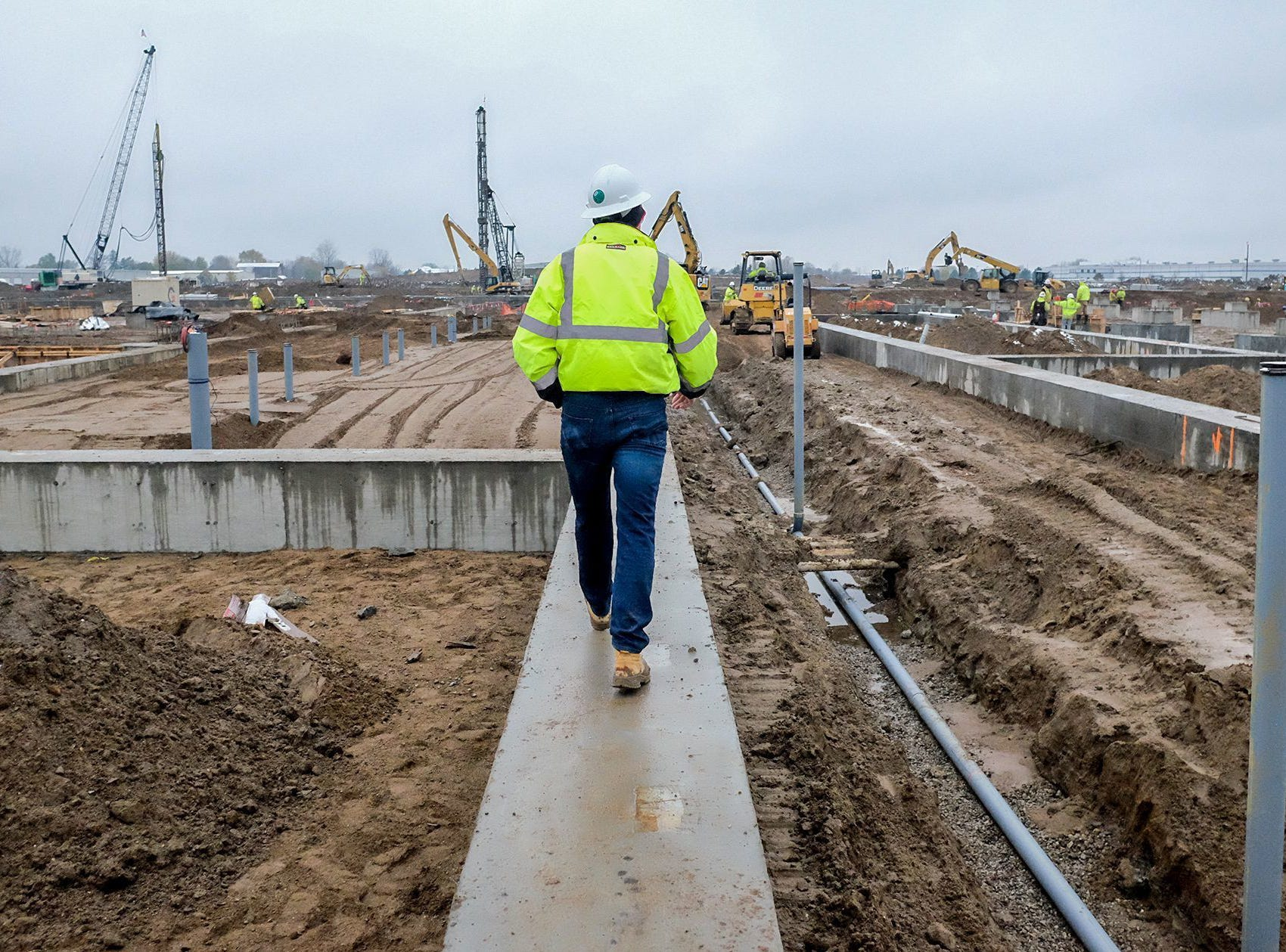 John Murphy, project manager for the new St. Johns cheese factory, walks along the cement footings as construction continues on the $555-million plant that will employ around 300 people on Friday Nov. 9, 2018.