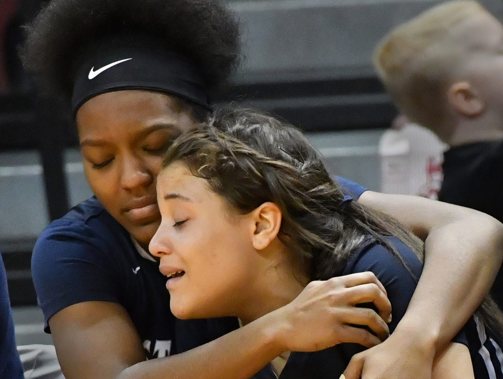 Zion Keyes, left, comforts teammate Amelia McNutt in the closing seconds of the MHSAA Girls Basketball Finals on Saturday, March 17, 2018 in Grand Rapids. East Lansing lost 57-36 to Saginaw Heritage.