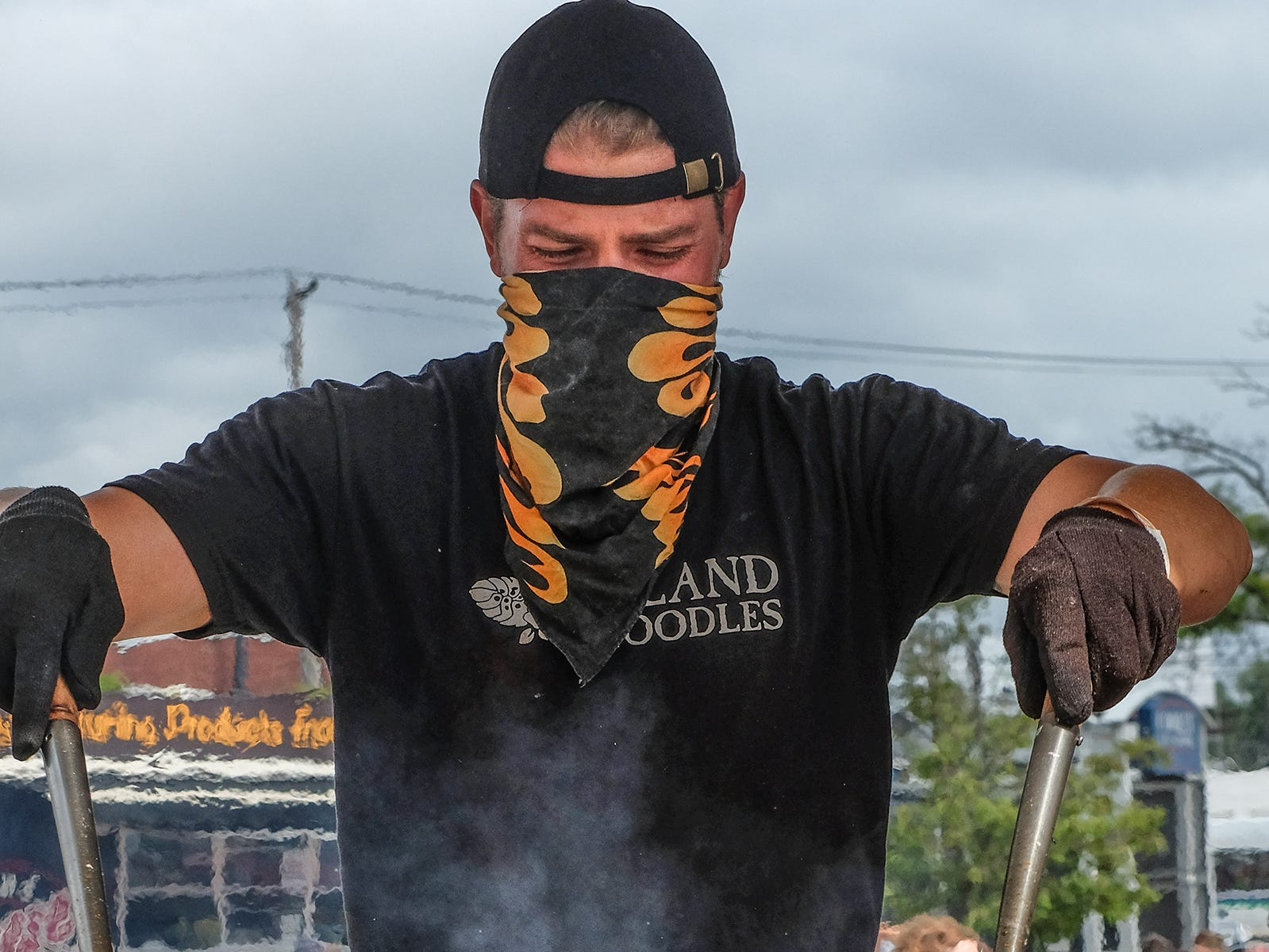 Jeremy Rowe from the Island Noodle food truck stirs up a fiery batch of vegetables and noodles at the Food Truck Mash-up on Saturday, Aug. 25, 2018 at Cooley Law School Stadium.