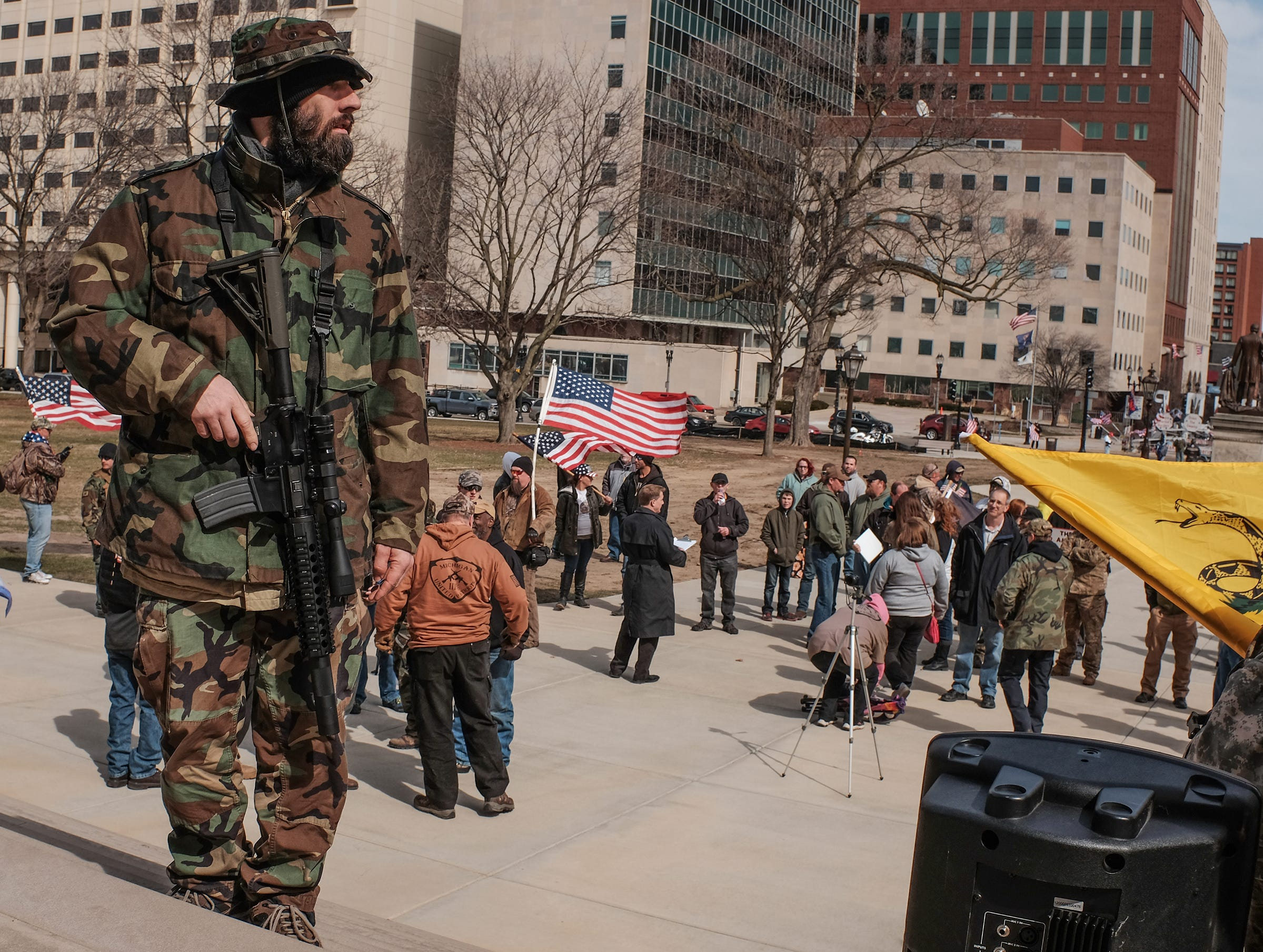 A man in camo clothing openly carries a weapon at a pro Second Amendment rally at the state Capitol in Lansing, Michigan on Saturday, March 24, 2018.