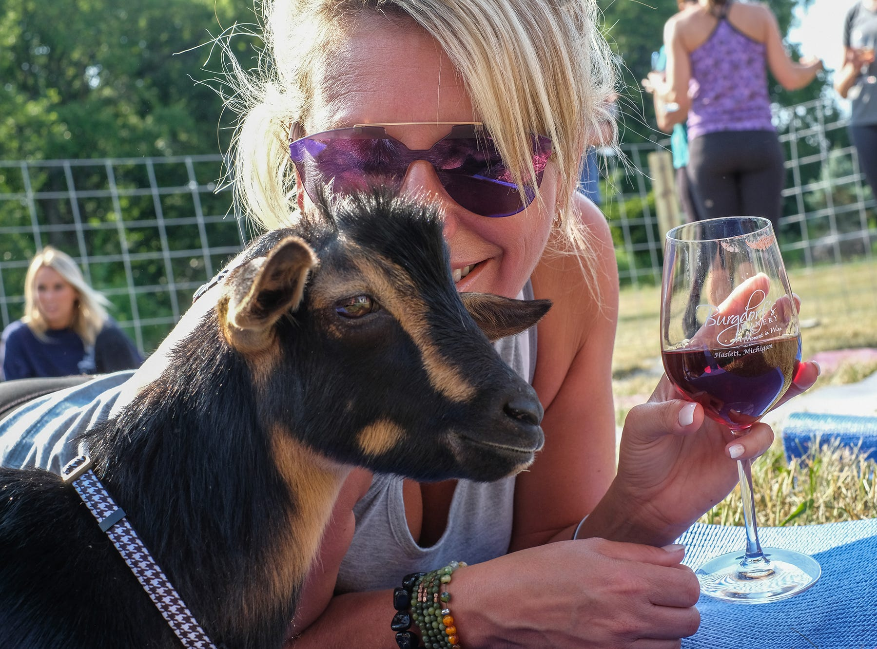 "Samantha Bense visiting from Palm Beach, Florida, gets some ""goat time"" after taking a Goat Yoga MI lesson at Burgdorf's Winery in Haslett on Saturday, July 28, 2018."