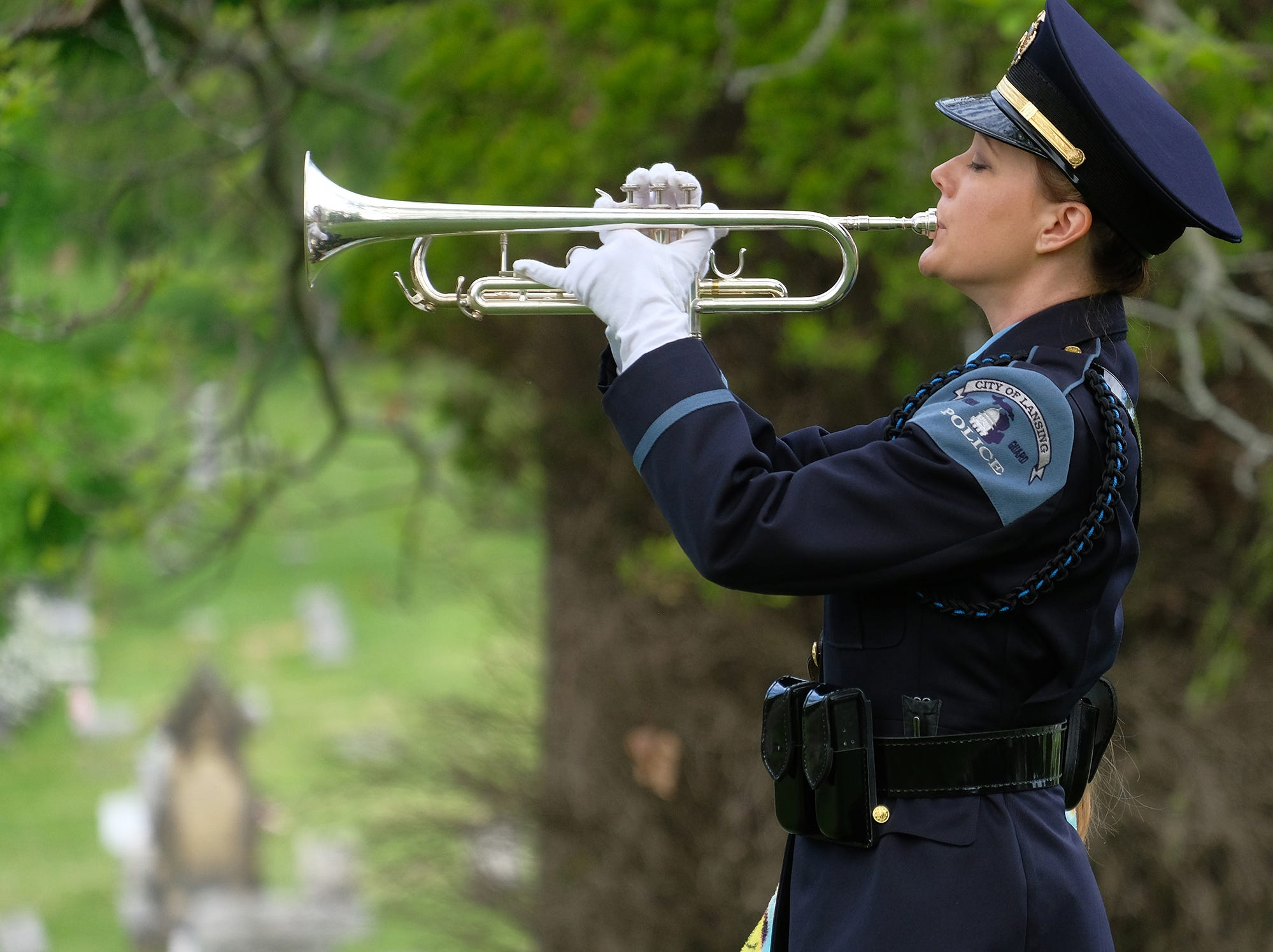 "Lansing Police Department Det. Shannon Thielen plays ""Taps"" at a Memorial Day Service at Mt. Hope Cemetery on Saturday, May 26, 2018."