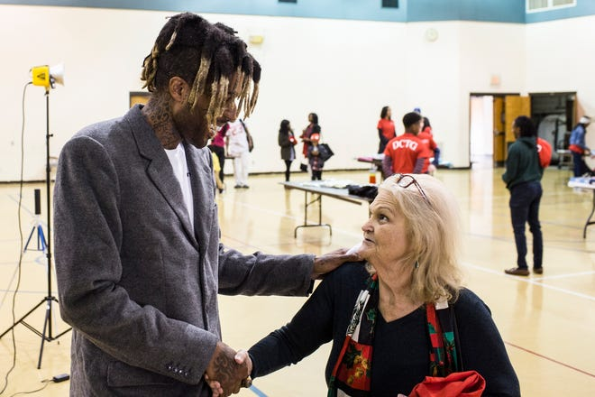 Supreme Bey, the Memphis basketball player formerly known as Chris Douglas-Roberts, shakes hands with Tigers fan Geneva Fort during a holiday gift giving event Sunday at the Capleville United Methodist Church Gym.
