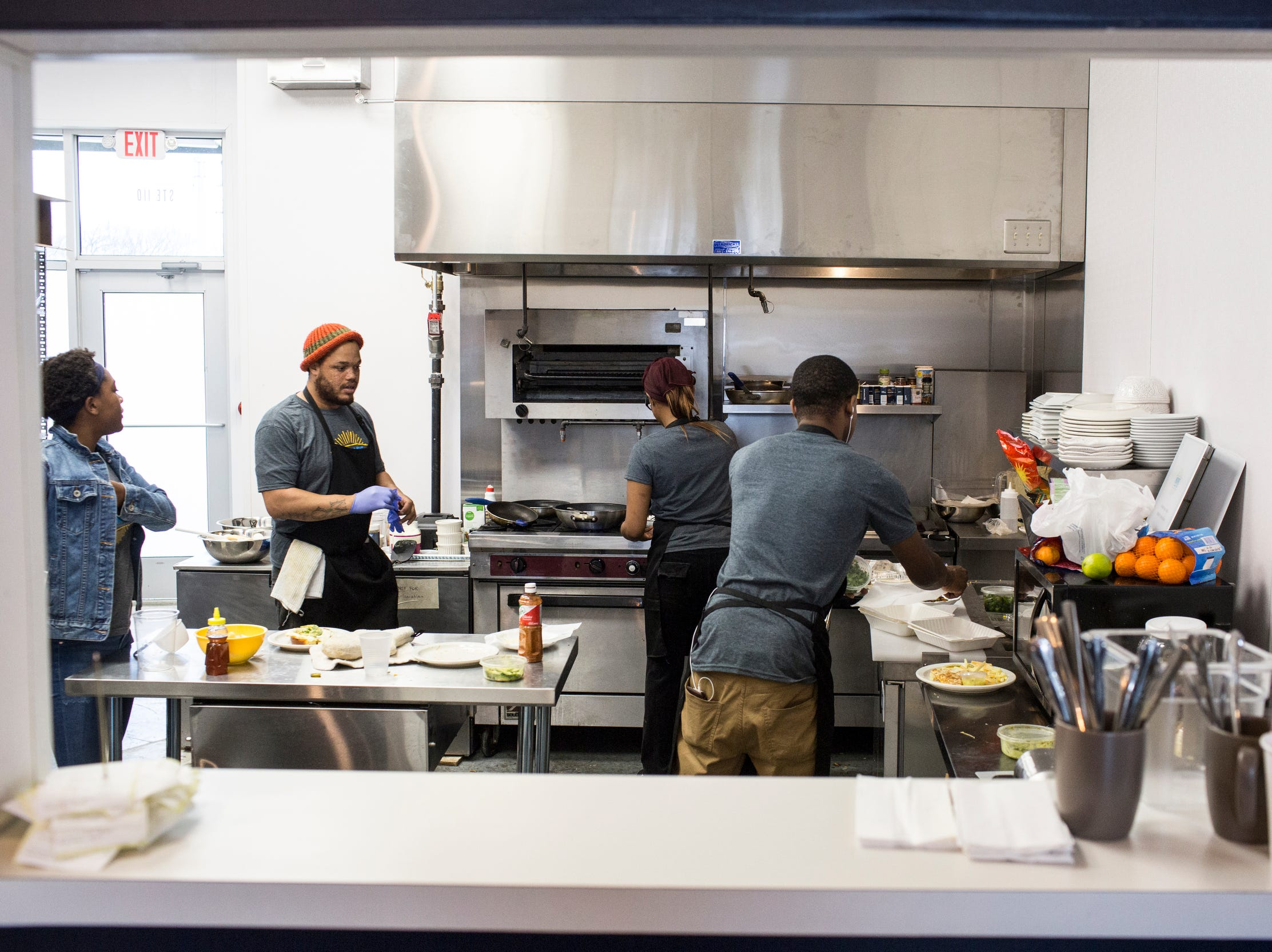 December 23 2018 - People work in the kitchen at Inspire Community Cafe during the final of three friends & family soft openings before the cafe opens January 4th.