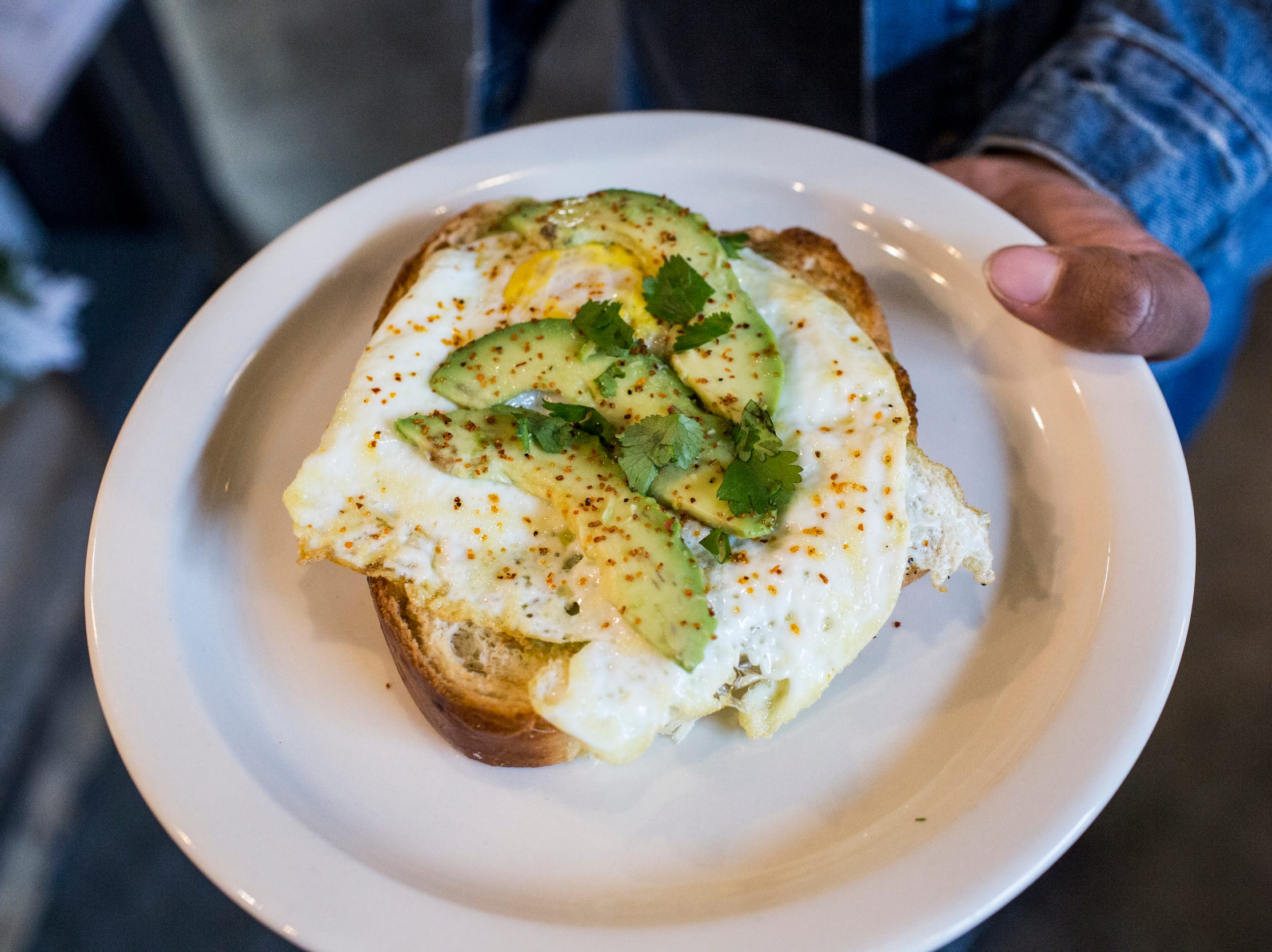 December 23 2018 - Avocado Toast featuring local baked bread, avocado, a fried egg, sea salt and tajin is seen at Inspire Community Cafe during the final of three friends & family soft openings before the cafe opens January 4th.