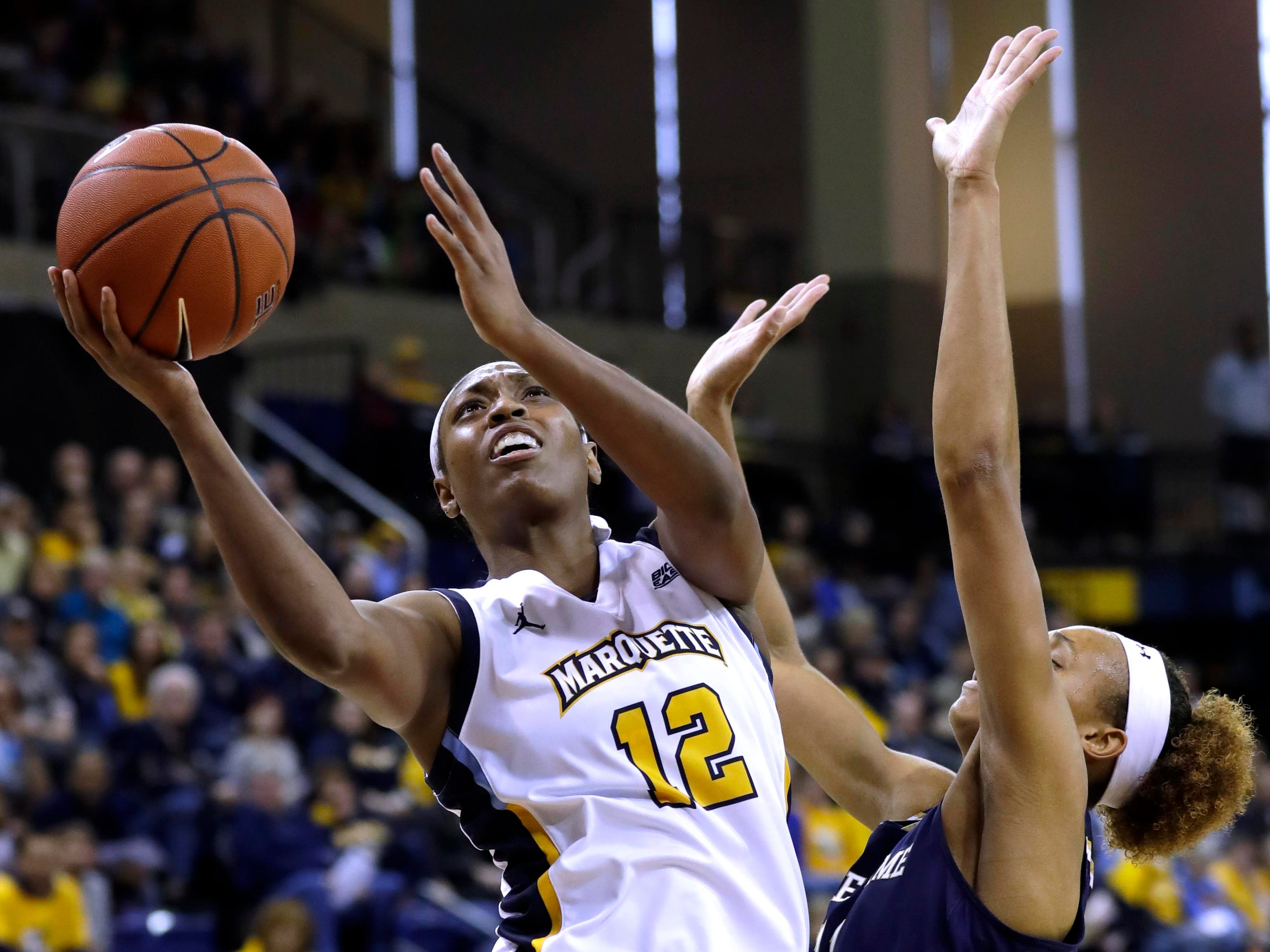 Marquette forward Erika Davenport scores on a drive to the basket.
