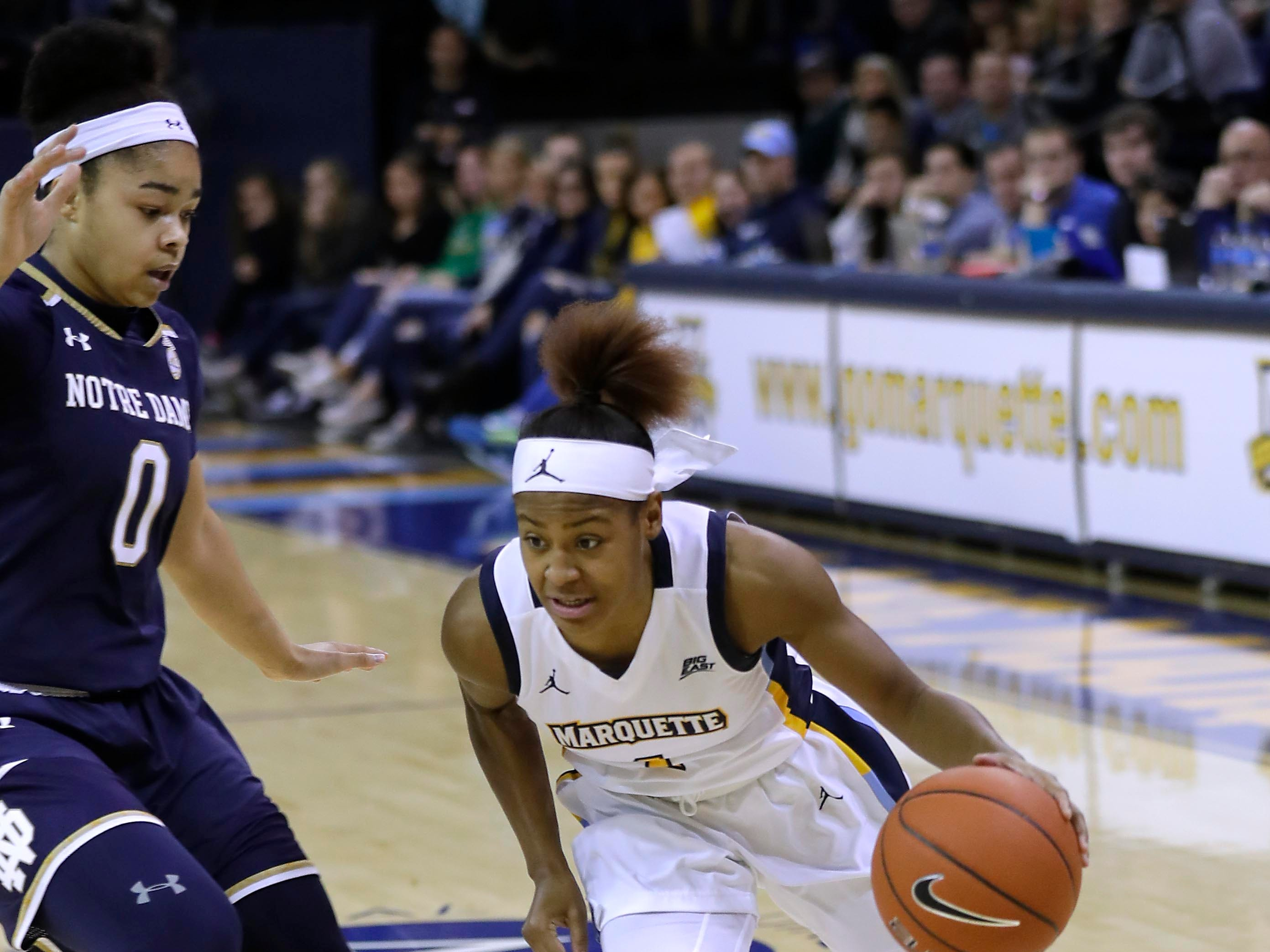 Marquette guard Danielle King drives to the basket past Notre Dame Fighting Irish guard Jordan Nixon.