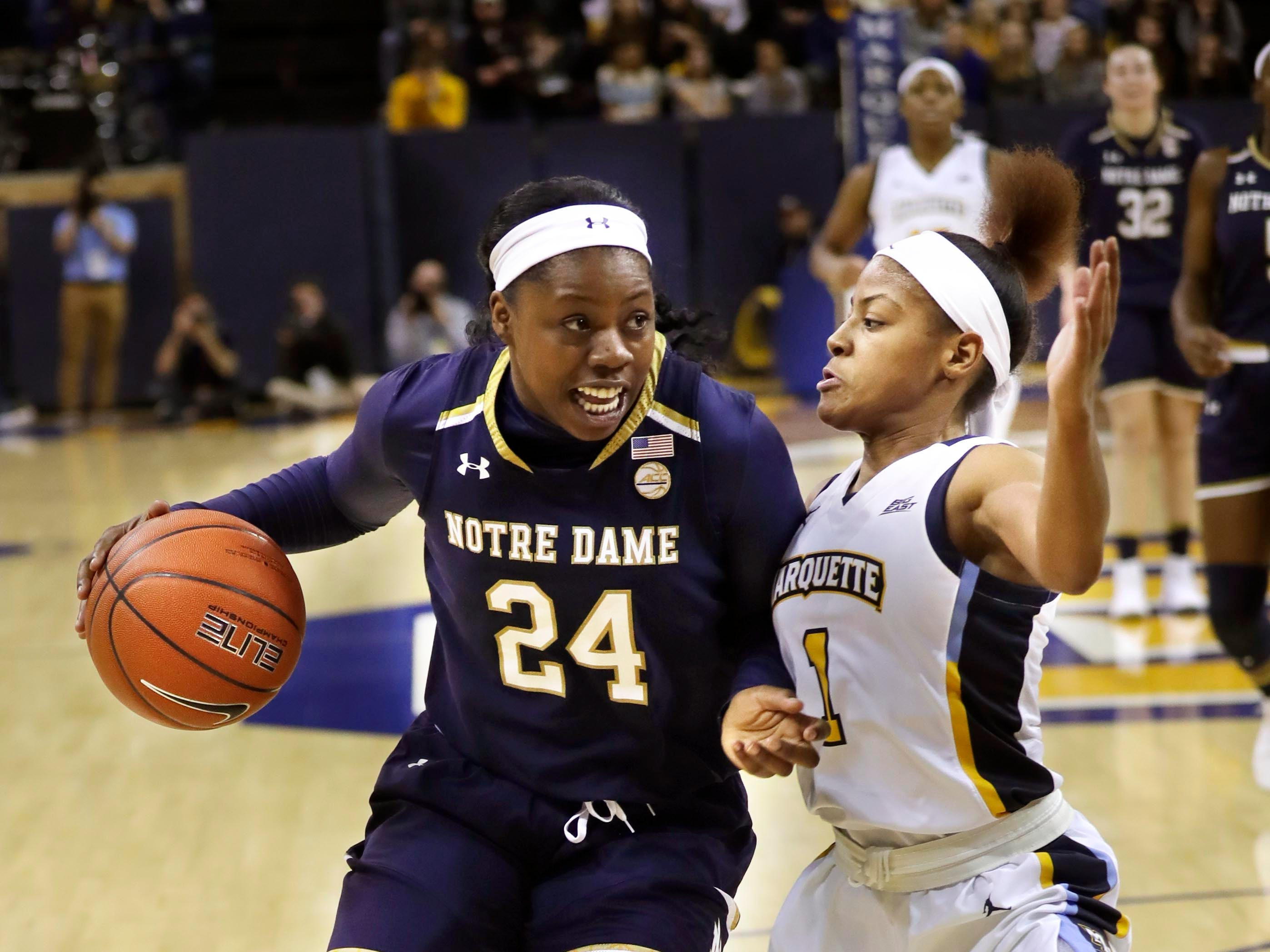 Notre Dame Fighting Irish guard Arike Ogunbowale  drives past  Marquette Golden Eagles guard Danielle King.