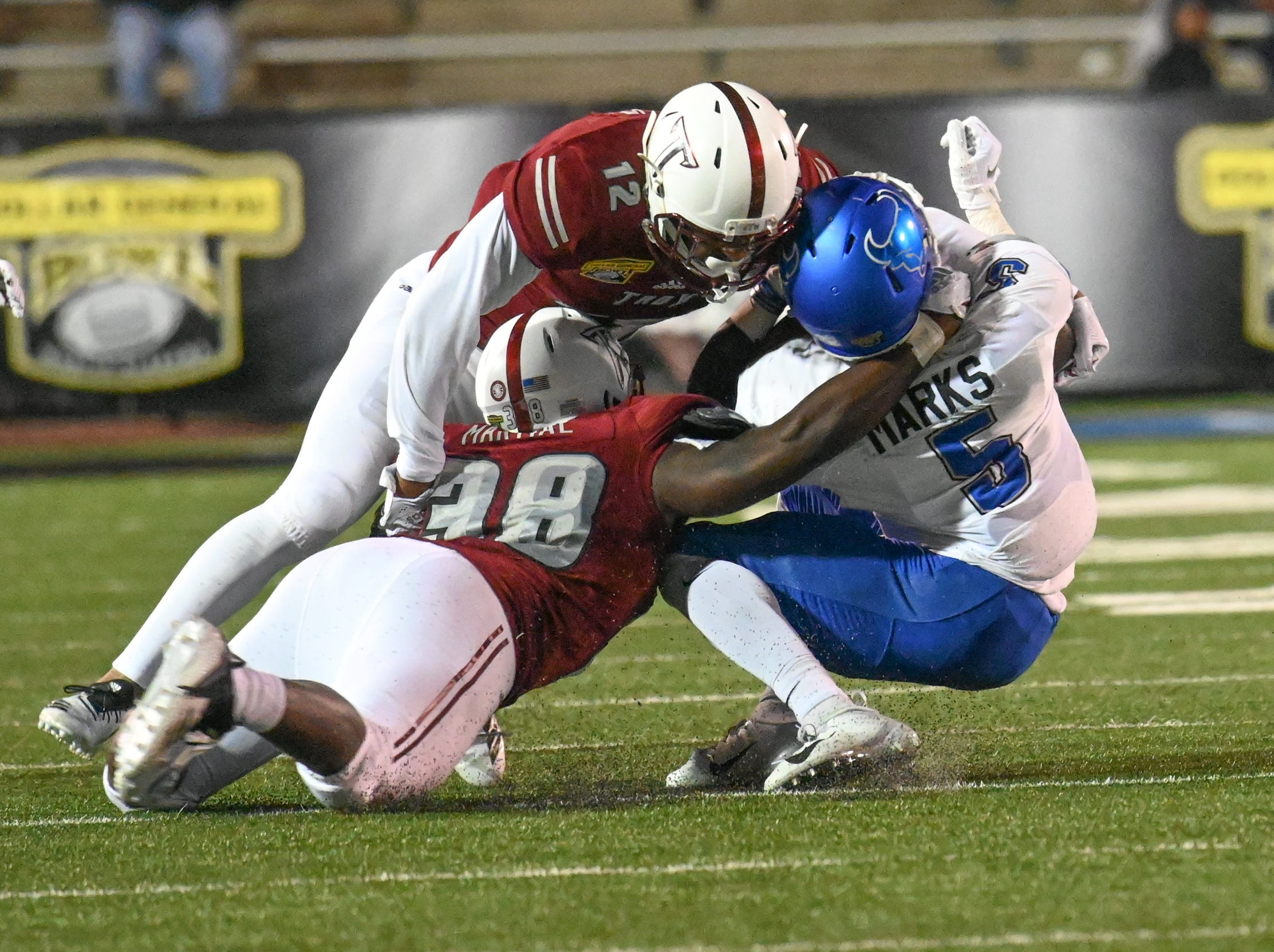 Buffalo Bulls running back Kevin Marks (5) is tackled by Troy Trojans safety Melvin Tyus (12) and Troy Trojans linebacker Carlton Martial (38) during the Dollar General Bowl held at Ladd-Peebles Stadium in Mobile on Saturday, Dec. 22, 2018.