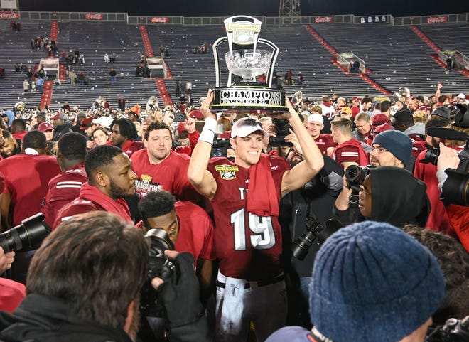 Troy Trojans fourth-string quarterback Kade Young (19) celebrates with teammates and fans after the Dollar General Bowl at Ladd-Peebles Stadium in Mobile on Saturday, Dec. 22, 2018.
