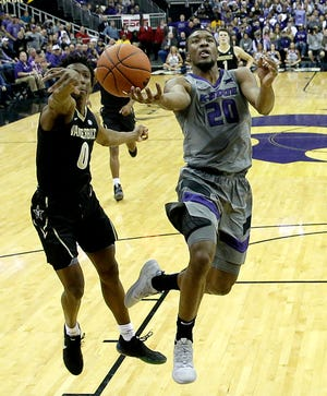Vanderbilt's Saben Lee (0) blocks a shot by Kansas State's Xavier Sneed (20) during the first half of an NCAA college basketball game Saturday, Dec. 22, 2018, at the Sprint Center in Kansas City, Mo.