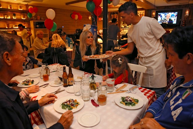 Milos Jokanovic serves pizza to guests at La Trattoria which opened Friday, Dec. 21, 2018, on Fifth Avenue South in downtown Naples.
