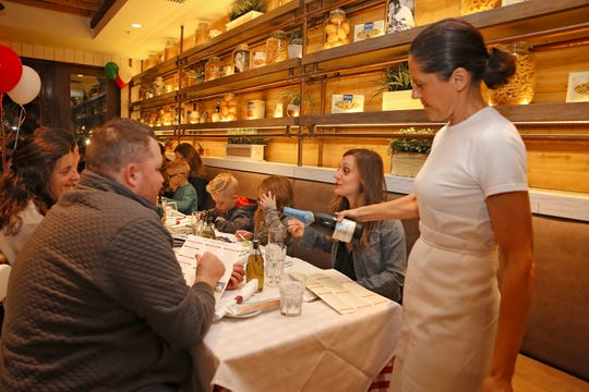 Barbara Gallone serves wine to guests at La Trattoria, which opened Friday, Dec. 21, 2018, on Fifth Avenue South in downtown Naples.