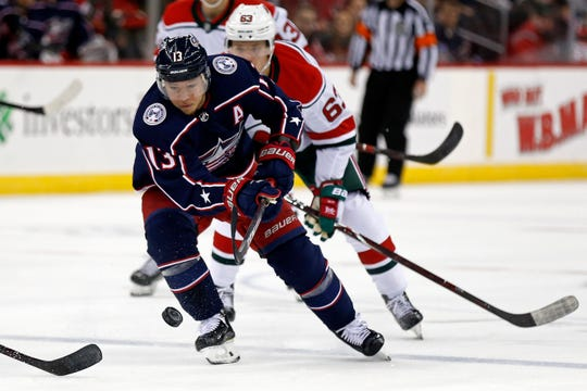 Columbus Blue Jackets right wing Cam Atkinson controls the puck against the New Jersey Devils during the first period of an NHL hockey game Sunday, Dec. 23, 2018, in Newark, N.J.