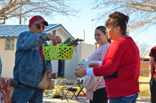 From left, Christmas in the Plaza volunteer Robert Gomez Jr. passes out a gift basket to Maria Dominguez.