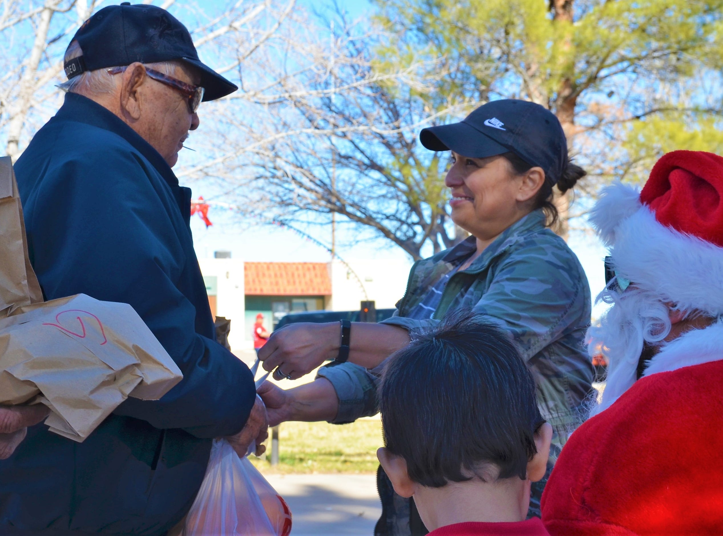 Victor Saez receives a bag of oranges from Christmas in the Plaza volunteer Julie Nicoley.