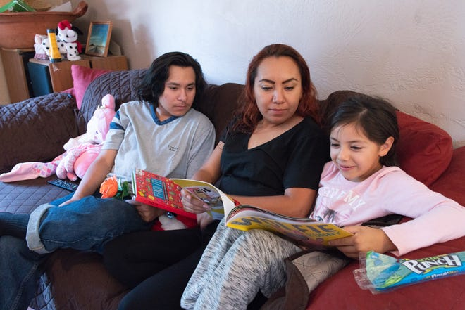 Nayeli and son Steven look on as Anabell, 6, reads a book.