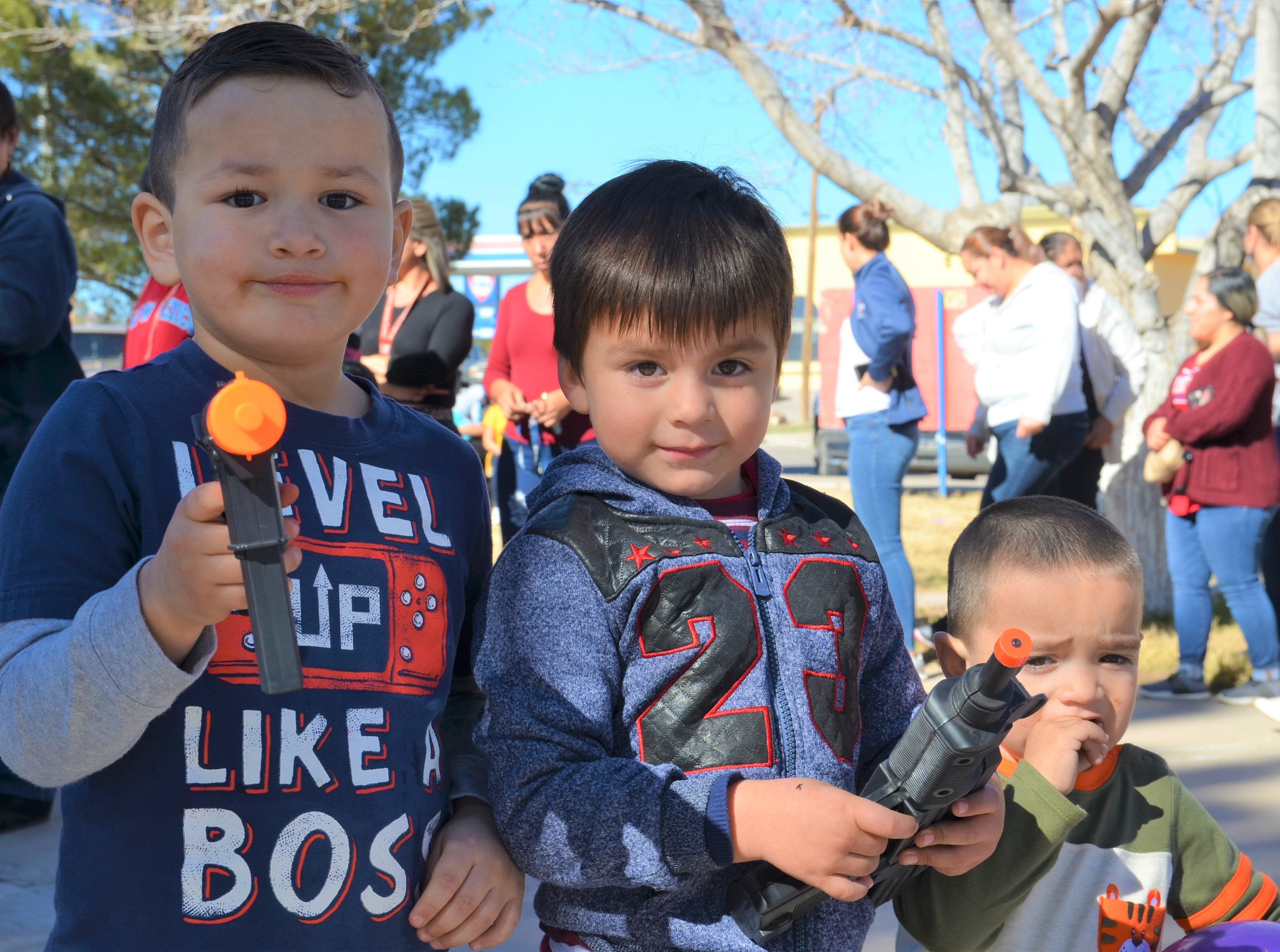 From left, Sebastian Ramos, 4, and Marco Antonio Ramos, 4 received toy guns while brother Gael Ramos, 2, received a purple ball.