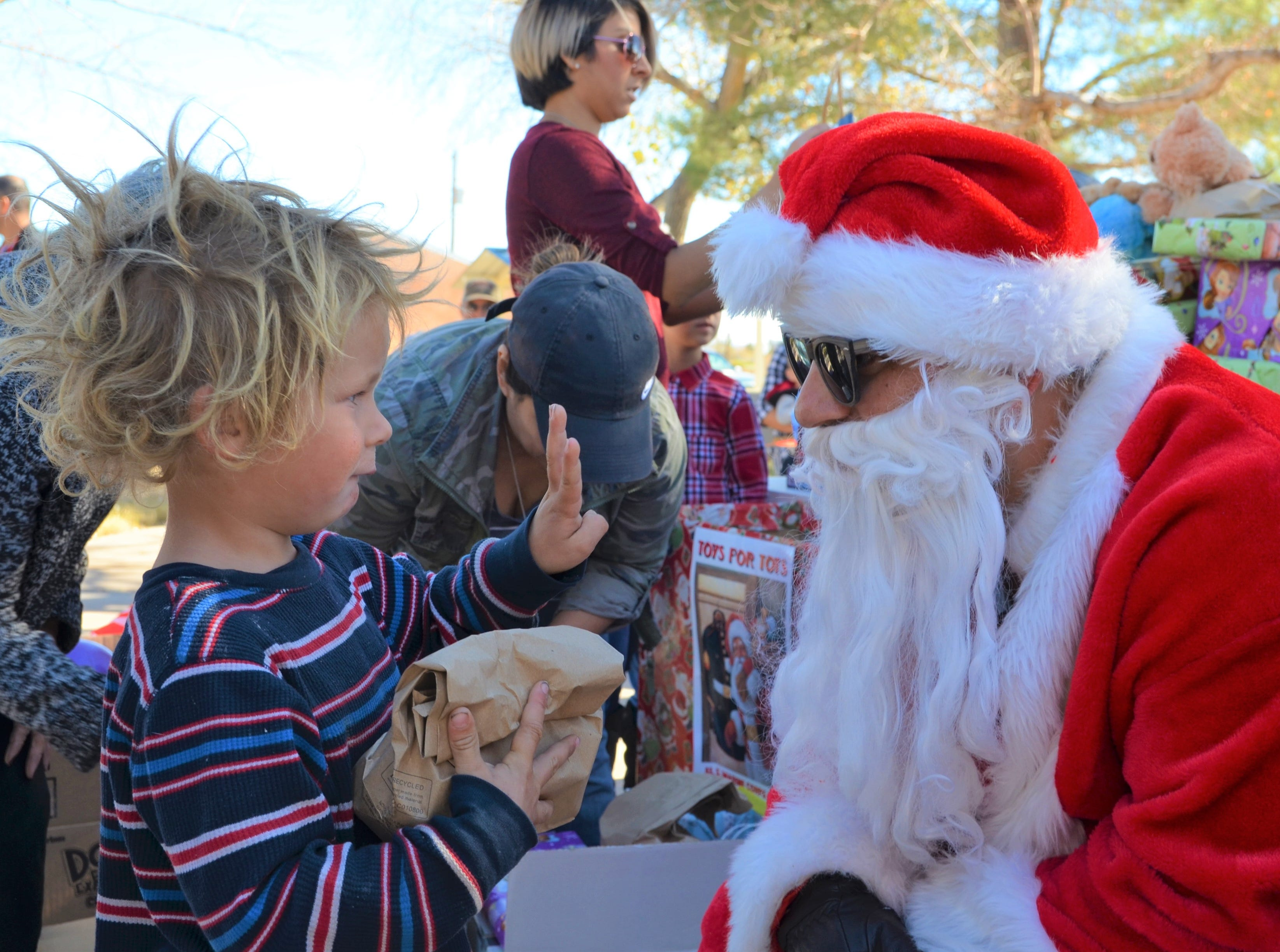 While meeting Santa Claus during the Christmas in the Plaza event, Tj, of 4, signals to the jolly man how old he is.
