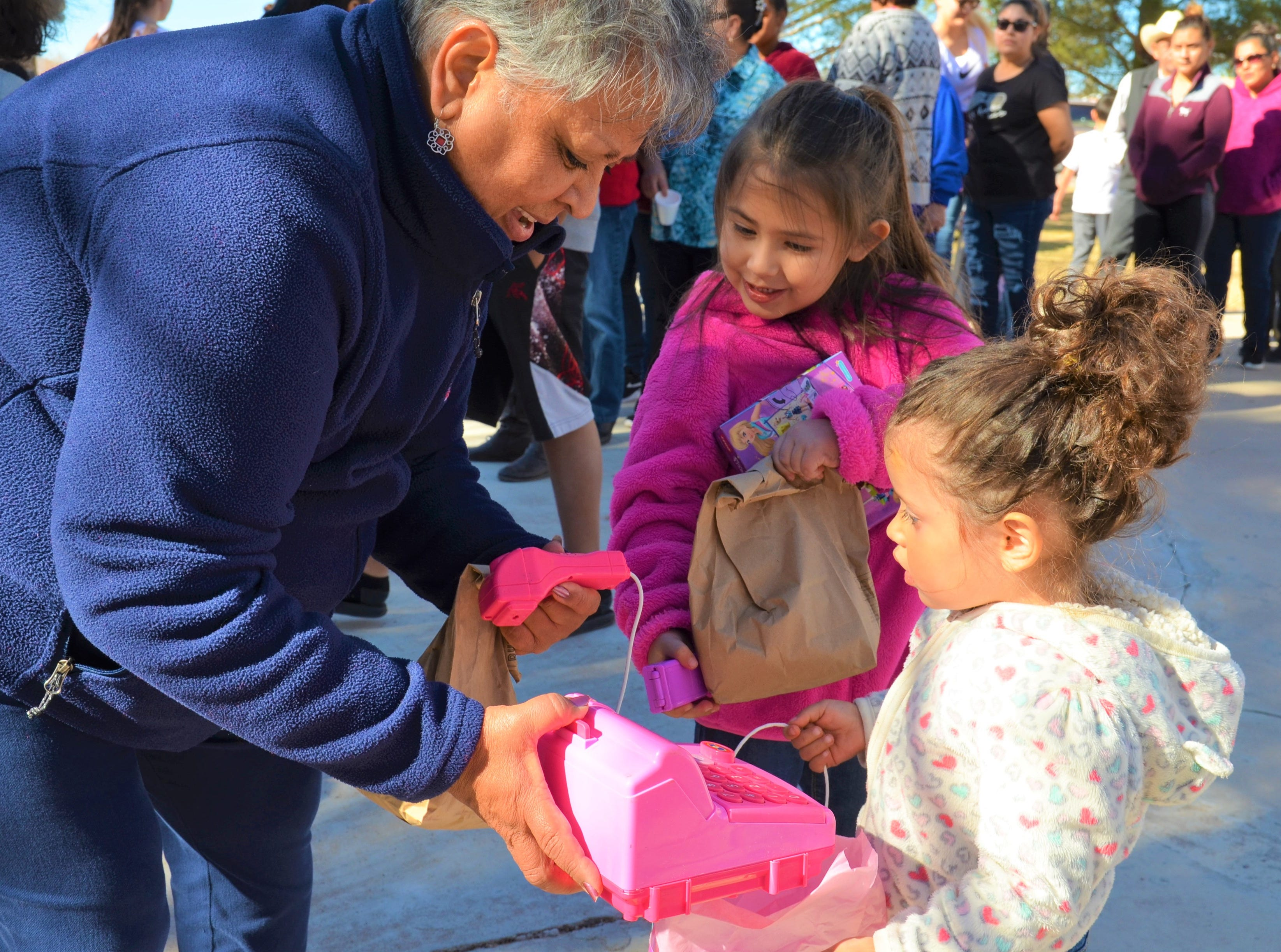 From left, grandma Carmen Porras, Mia Sanchez, 5, look to see what 2-year-old Carmen Sanchez has received from Santa Claus -- a toy cash register.