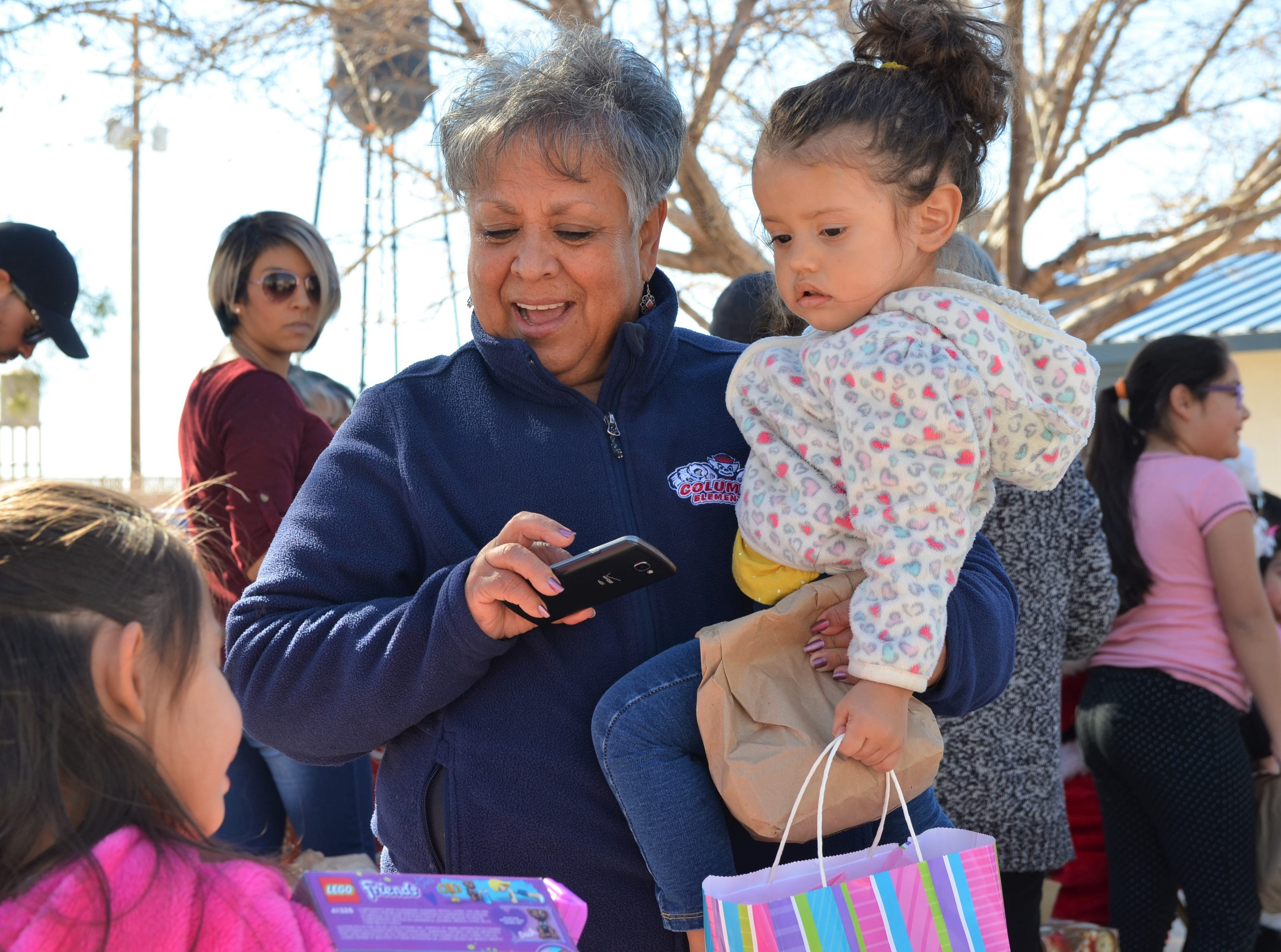 From middle to right, Carmen Porras and Carmen Sanchez, 2, look on to see what Mia Sanchez, 5, granddaughter and sister of the two has received from Santa.