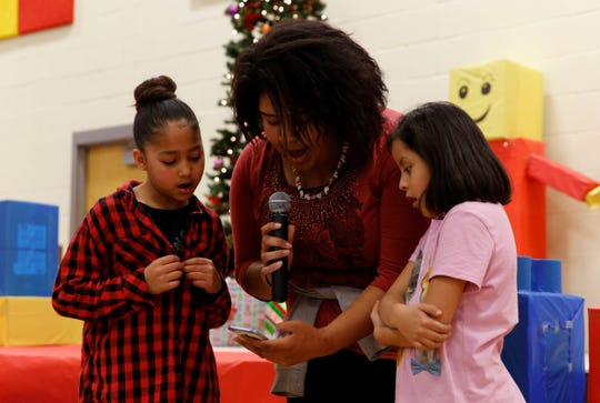 Dylan Dasher, left, and Alexis Deja Peters, right, help sing a Christmas carol during Operation Blessing on Saturday at the Shiprock Youth Complex.
